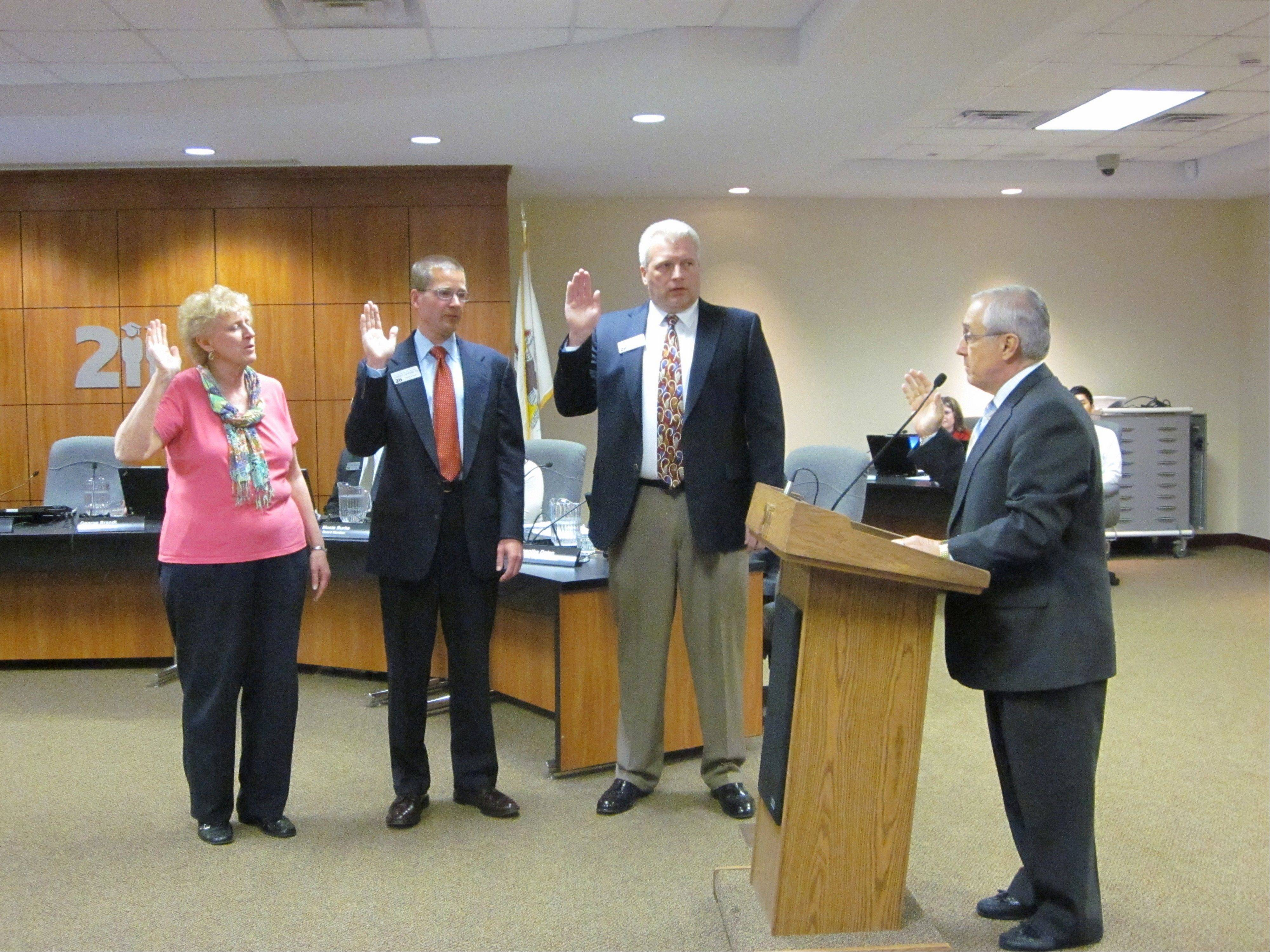 North Cook Intermediate Service Center Executive Director Robert Ingraffia, right, administers the oath of office to Anna Klimkowicz, left, Robert LeFevre, second to left, and Mike Scharringhausen, second to right, during the Palatine-Schaumburg High School District 211 board of education meeting Thursday.
