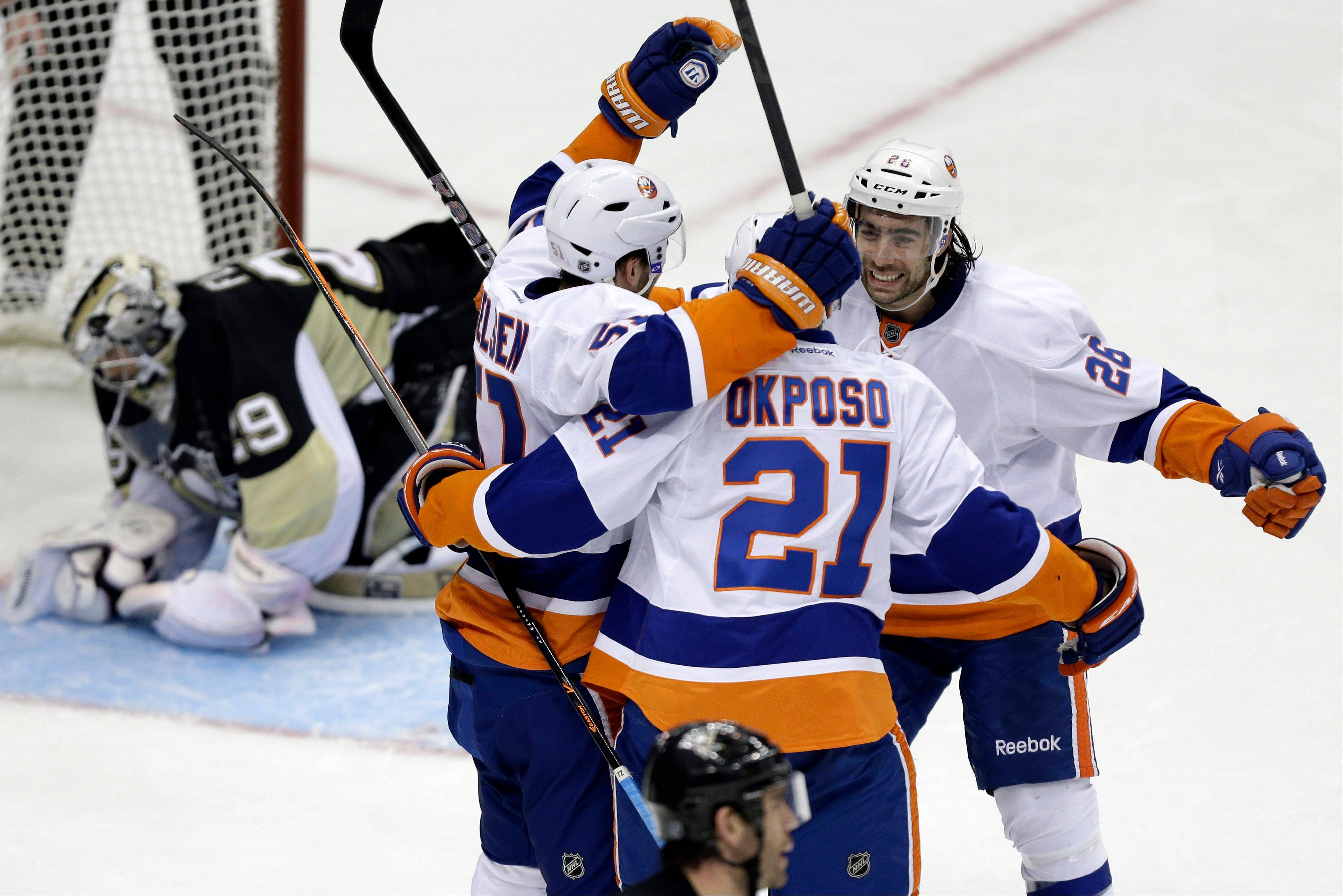 New York Islanders' Kyle Okposo (21) celebrates his goal with teammates Matt Moulson (26) and Frans Nielsen (51) as Pittsburgh Penguins goalie Marc-Andre Fleury (29) collects himself during the third period of Game 2 of an NHL hockey Stanley Cup first-round playoff series, Friday, May 3, 2013, in Pittsburgh. The Islanders won 4-3 to even the series at 1-1.(AP Photo/Gene J. Puskar)