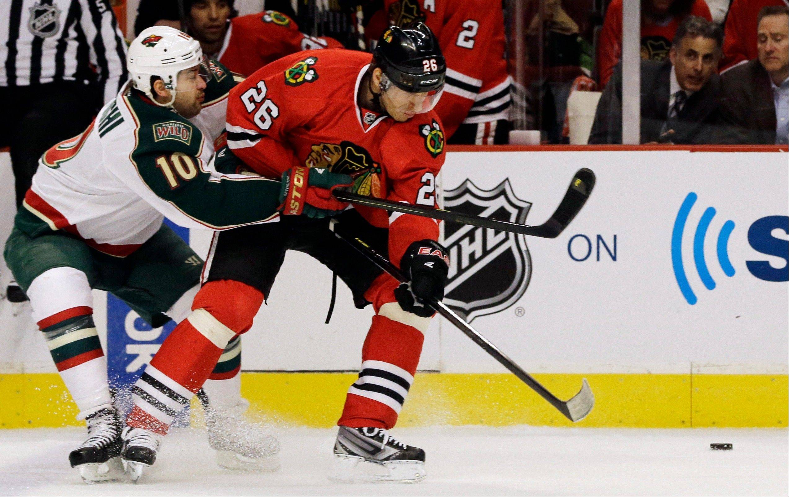 Minnesota Wild's Devin Setoguchi, left, battles for the puck with Chicago Blackhawks' Michal Handzus during the first period of Game 2 of an NHL hockey Stanley Cup first-round playoff series in Chicago, Friday, May 3, 2013. (AP Photo/Nam Y. Huh)