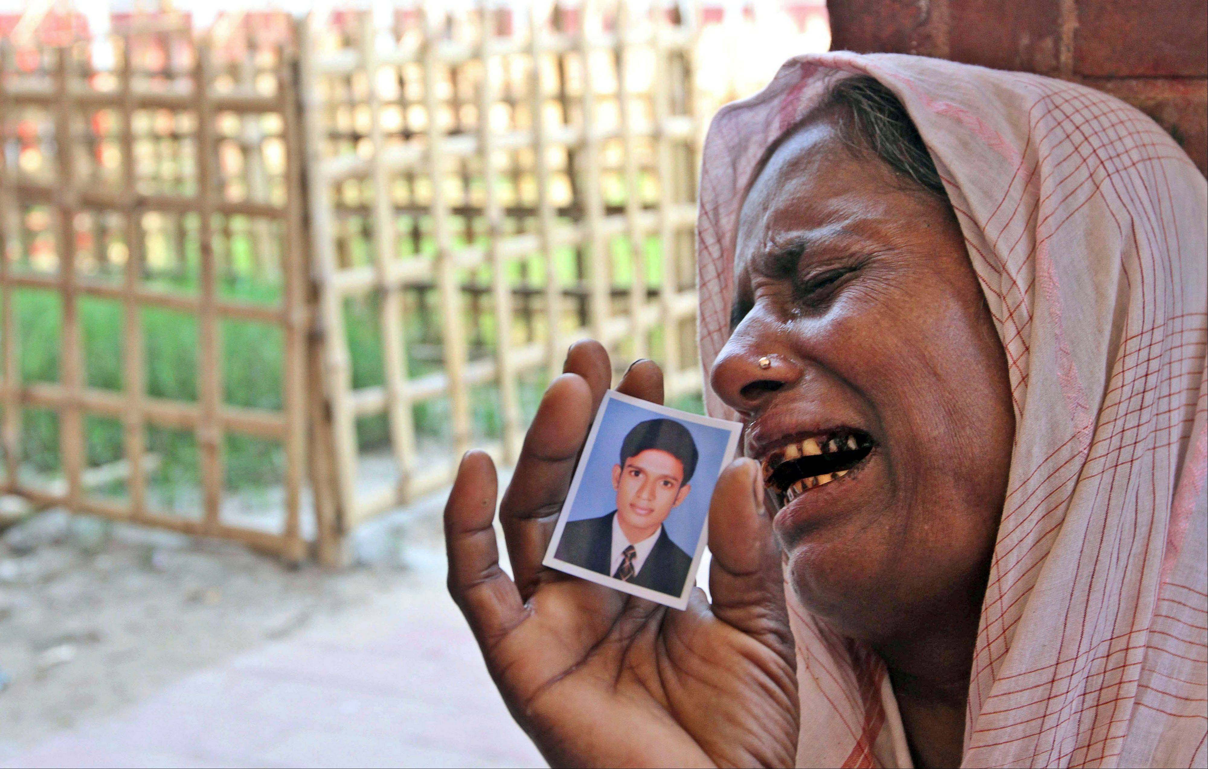 A Bangladeshi woman, holding a photo of her missing son, cries at a graveyard after a garments factory building collapse in Savar near Dhaka, Bangladesh, Friday May 3, 2013.