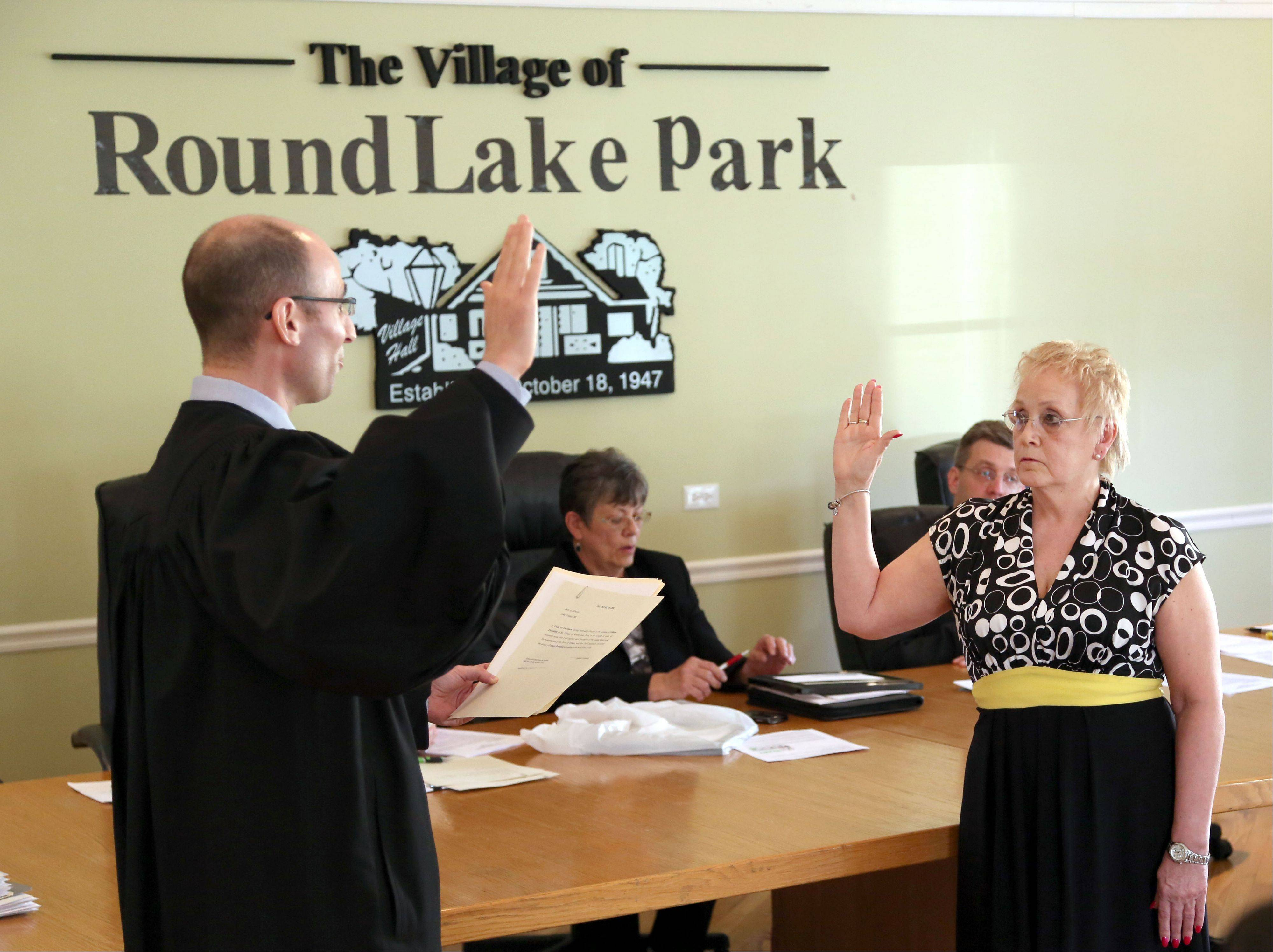 Linda Lucassen, right, is sworn in as the new mayor of Round Lake Park by Lake County Circuit Court Judge Daniel B. Shanes during their village board meeting Tuesday night.