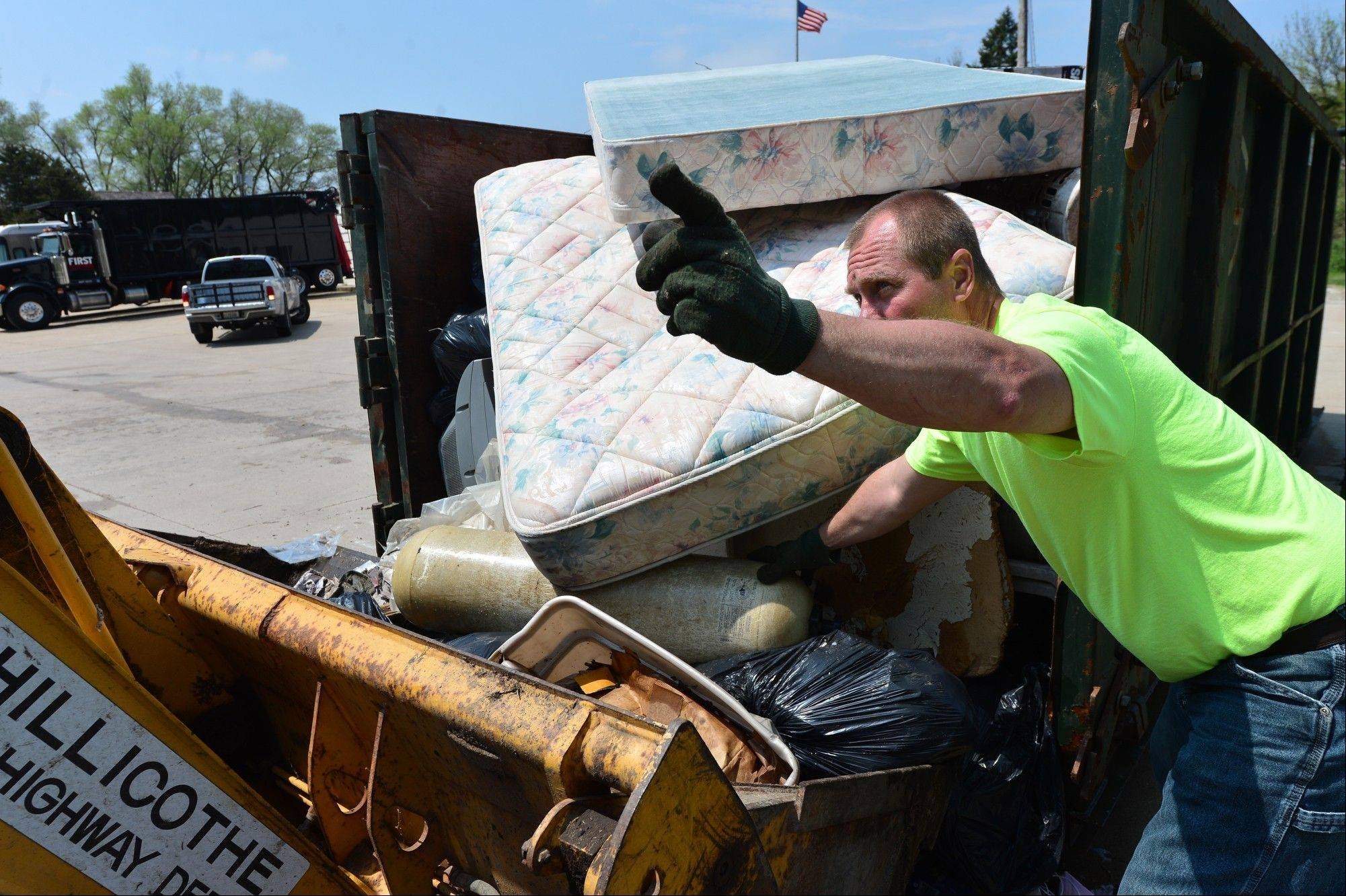 Chillicothe worker Kevin Conarro motions to driver Jason Schrock as they handle flood debris dumped by homeowners in a dumpster outside of the Rome Post Office in Rome, Ill., Thursday, May 2, 2013.