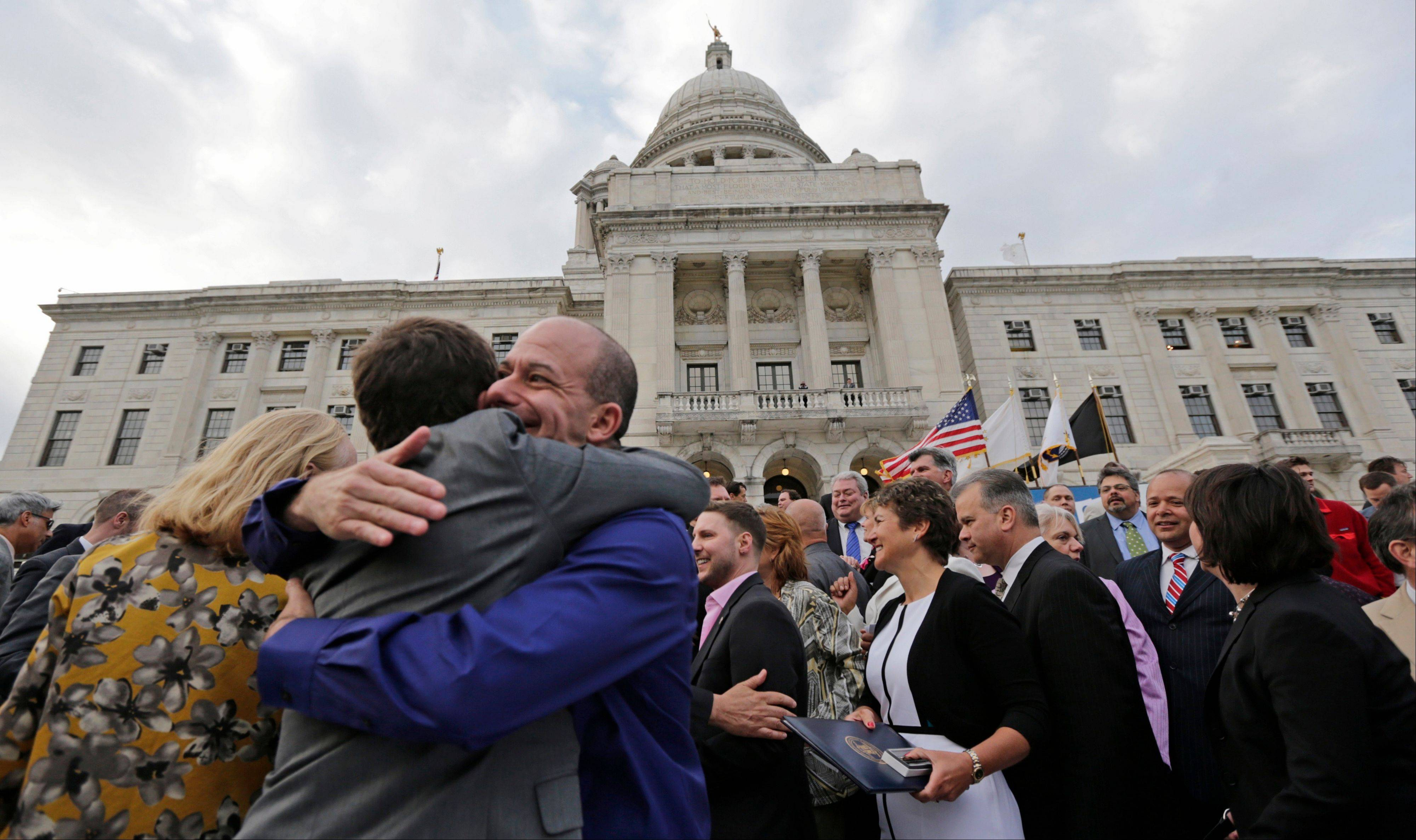 Two men embrace after a gay marriage bill was signed into law outside the State House in Providence, R.I., Thursday, May 2, 2013.