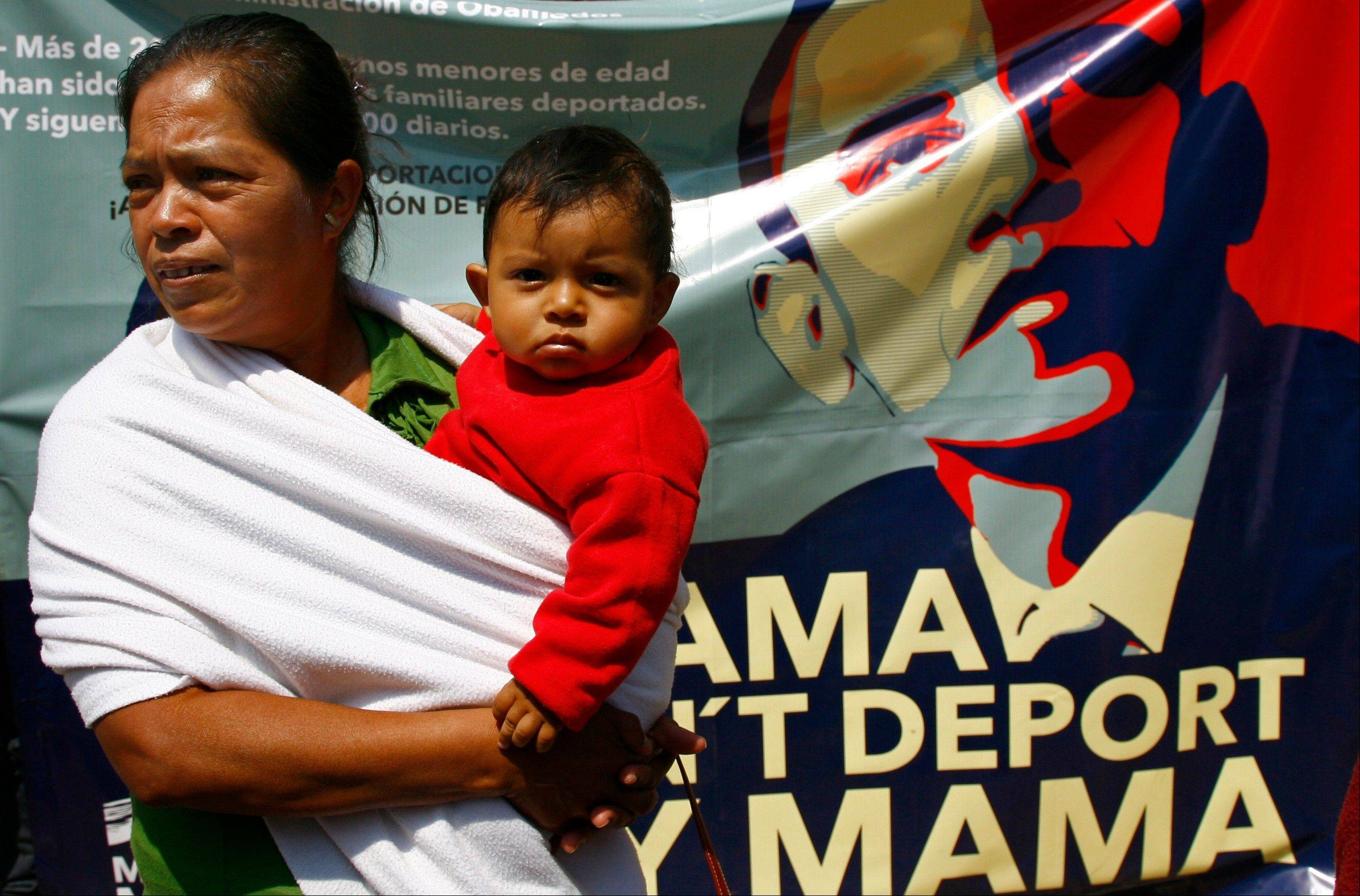 A woman holds her child as she attends a protest outside the U.S. embassy before the arrival of President Barack Obama in Mexico City, Thursday, May 2, 2013.