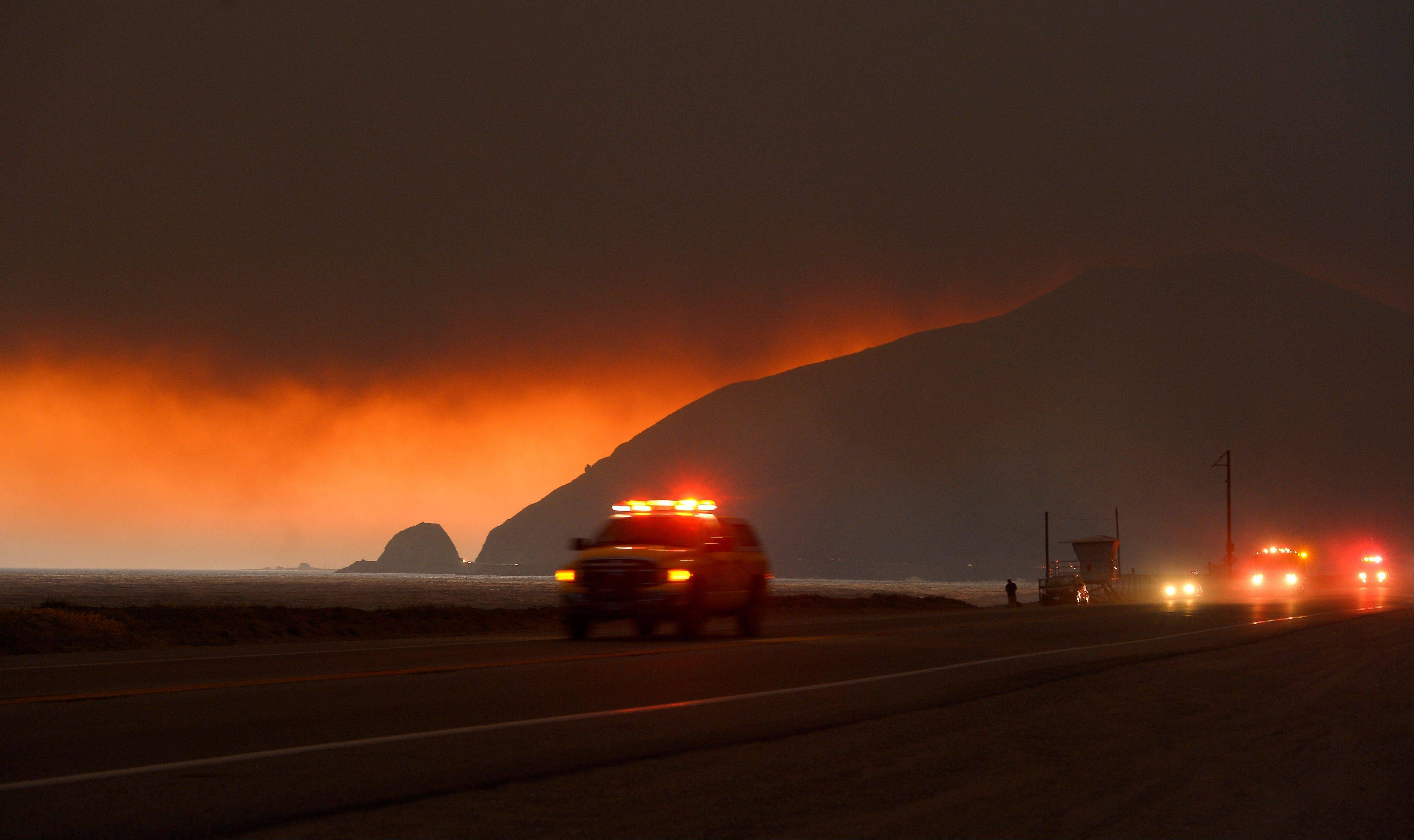 Fire department personnel drive along Pacific Coast Highway near Point Mugu as a thick layer of smoke sits overhead during a wildfire that burned several thousand acres, Thursday, May 2, 2013, in Ventura County, Calif.