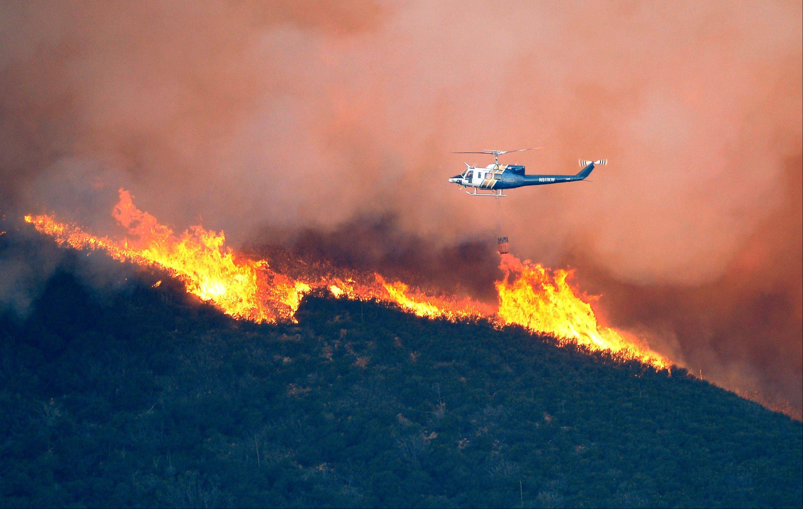 A water dropping helicopter gets ready to make a drop on a fire burring in Point Mugu State Park during a wildfire that burned several thousand acres, Thursday, May 2, 2013, in Ventura County, Calif.