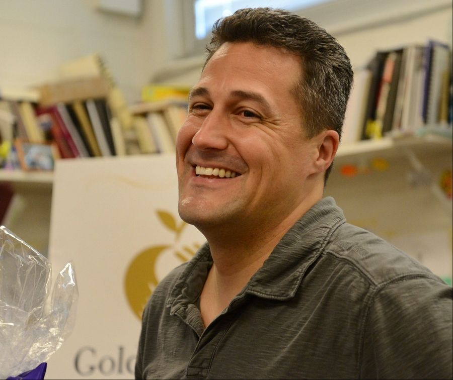 Gregory Regalado, who teaches courses in art, photography and design at Maine West High School, received his Golden Apple Award on Wednesday at the Des Plaines school.