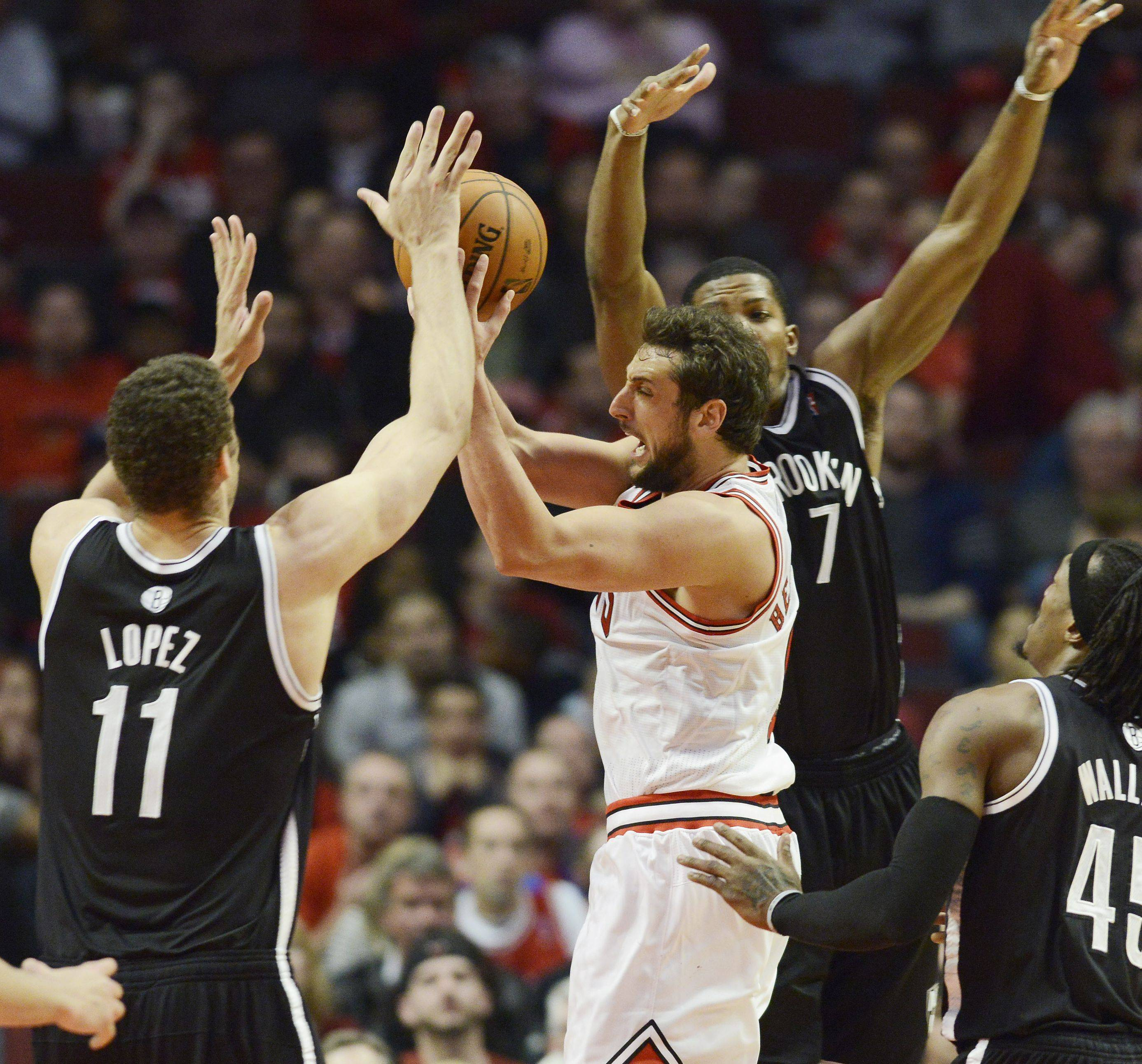 Marco Belinelli drives hard to the basket against Brook Lopez, left, and Deron Williams during the Bulls' Game 6 loss Thursday at the United Center. Belinelli missed a potential game-tying 3-pointer in the waning seconds of the fourth quarter.