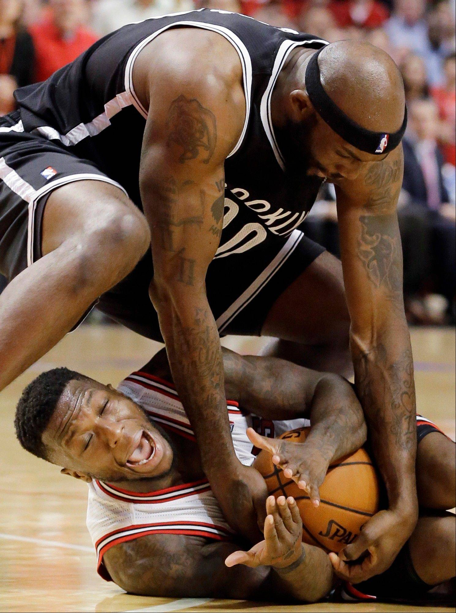 Brooklyn Nets forward Reggie Evans, top, and Chicago Bulls guard Nate Robinson battle for a loose ball during the second half in Game 6 of their first-round NBA basketball playoff series in Chicago, Thursday, May 2, 2013. The Nets won 95-92.