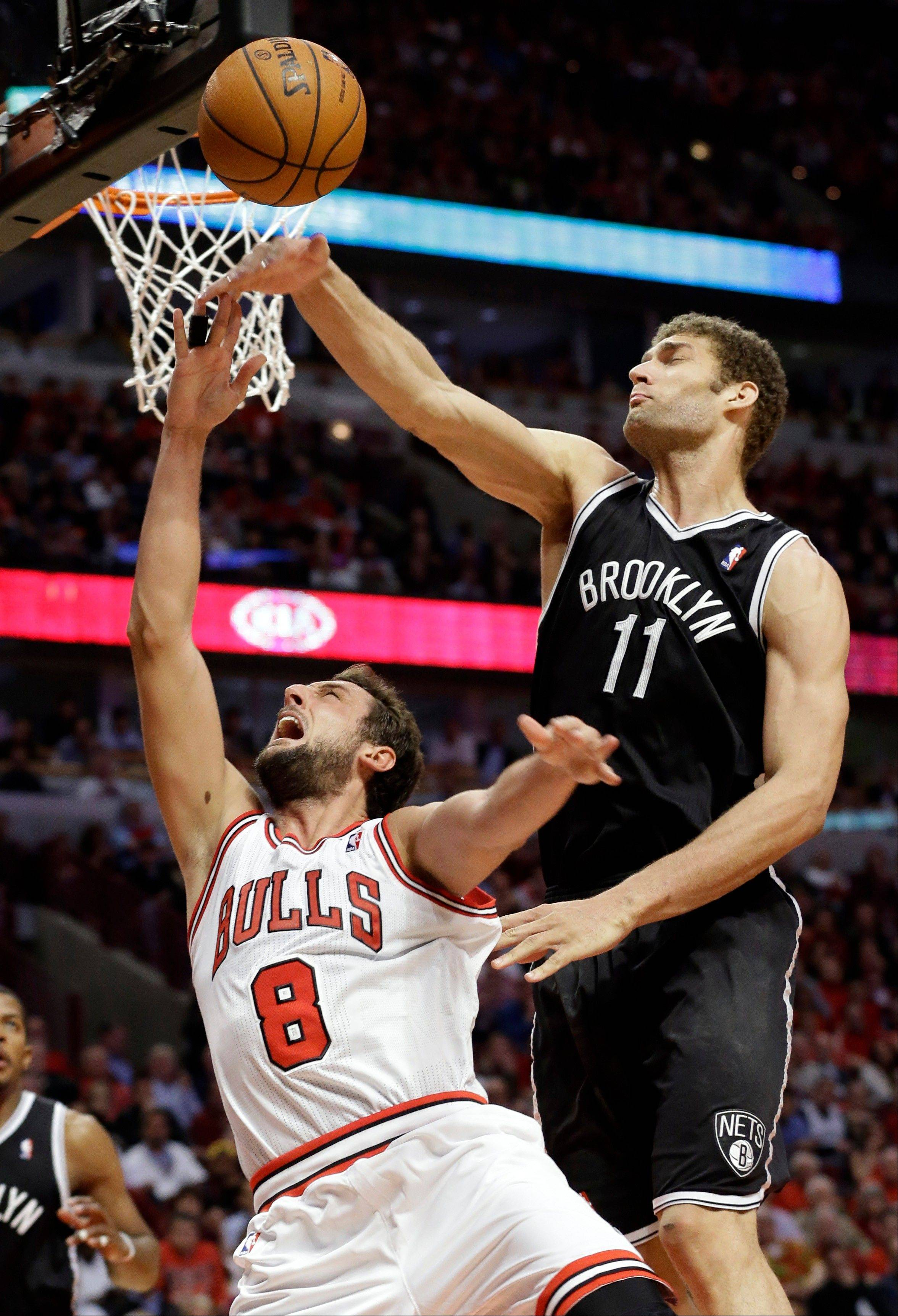 Brooklyn Nets center Brook Lopez (11) blocks a shot by Chicago Bulls guard Marco Belinelli, of Italy, during the second half in Game 6 of their first-round NBA basketball playoff series in Chicago, Thursday, May 2, 2013. The Nets won 95-92.