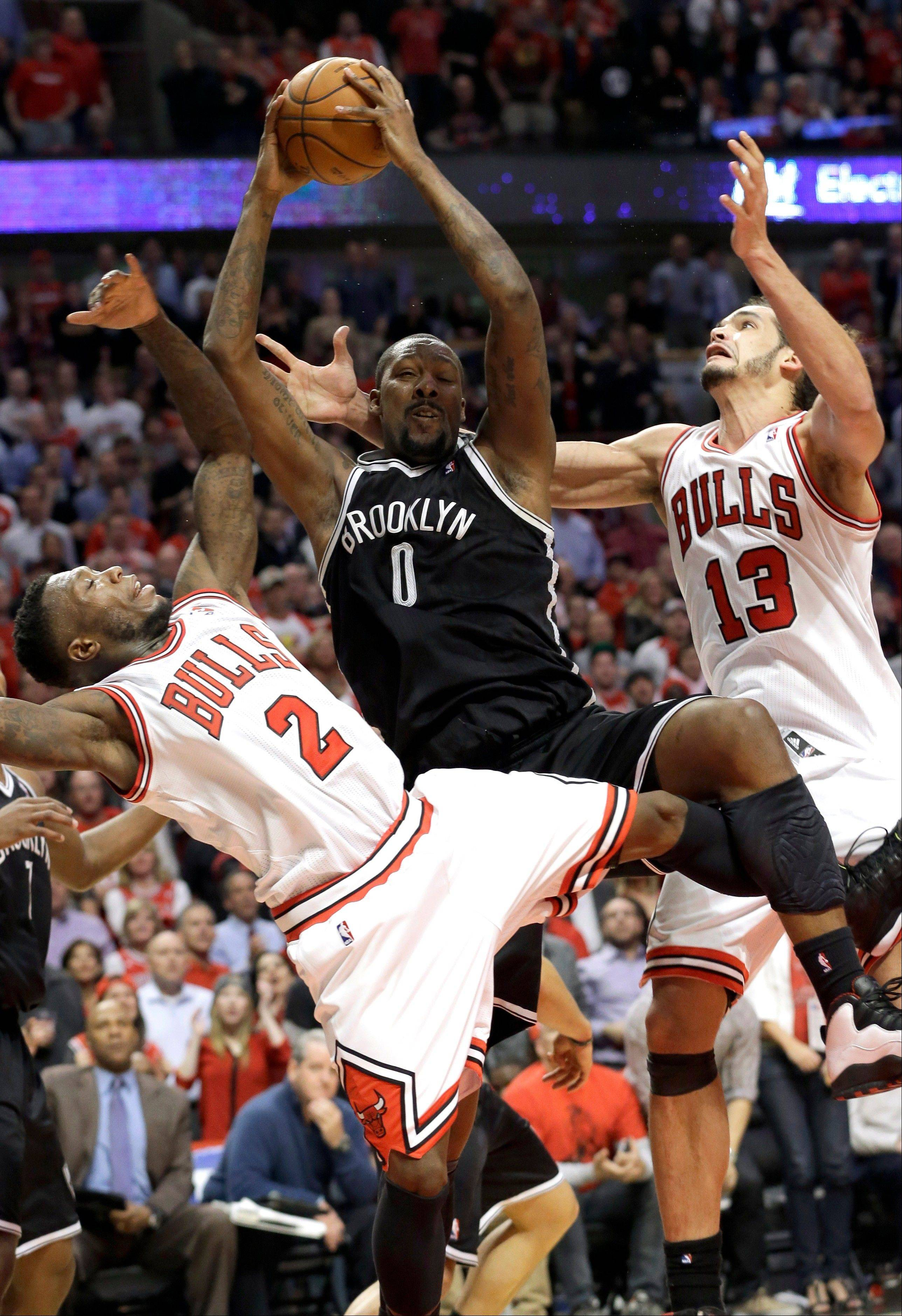 Nets forward Andray Blatche rebounds the ball between the Bulls' Nate Robinson (2) and center Joakim Noah during the second half of Game 6 of their first-round playoff series Thursday. Blatche's 2 late free throws gave the Nets a 3-point lead they would not relinquish.