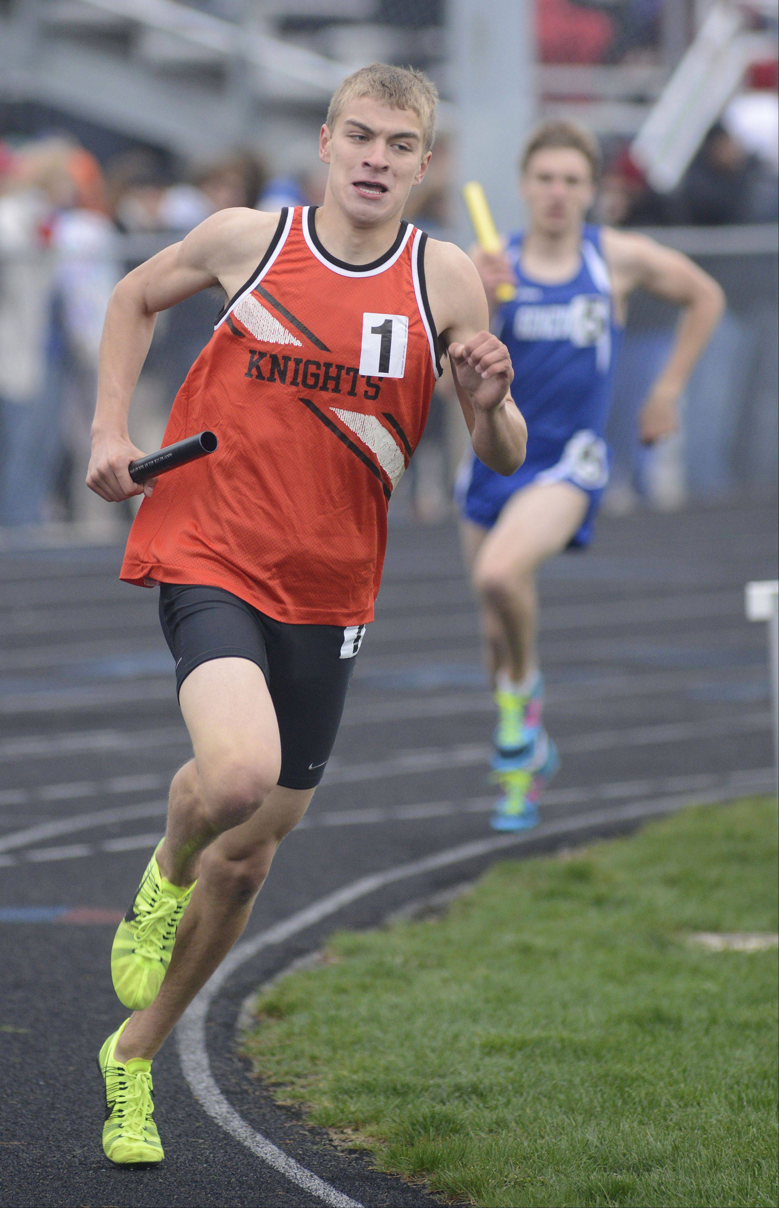 Kaneland's Nathaniel Kucera leads the 4 x 800 meter relay in the last lap with Geneva's Nathan Wendt on his trail at the Kane County Boys Track Meet at Burlington Central on Friday.