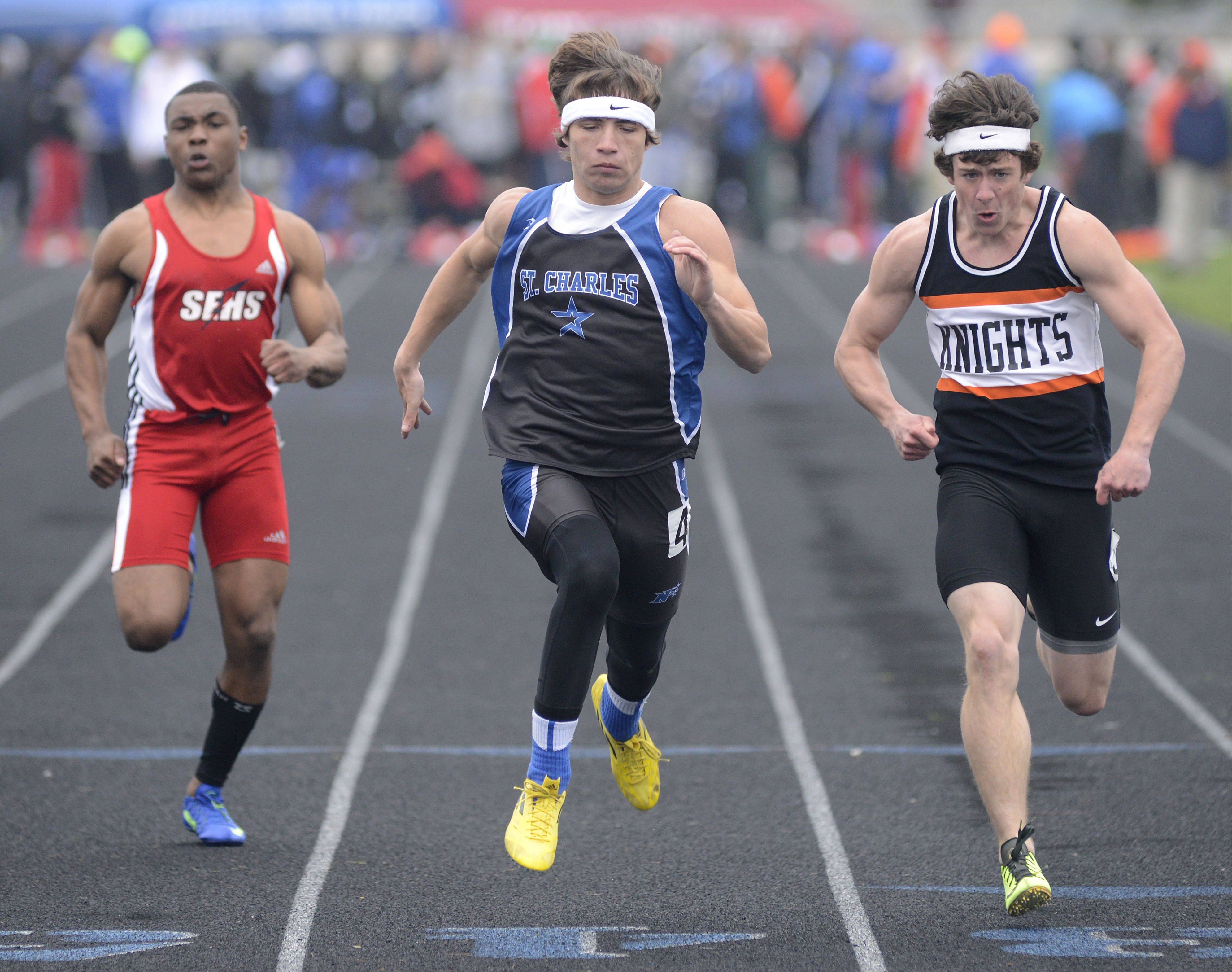 St. Charles North's Grant Loess takes the win in the final heat of the 100-meter dash at the Kane County boys track meet at Burlington Central on Friday. South Elgin's Shawn Griffin is on the left, and Kaneland's Brandon Bishop on the right.