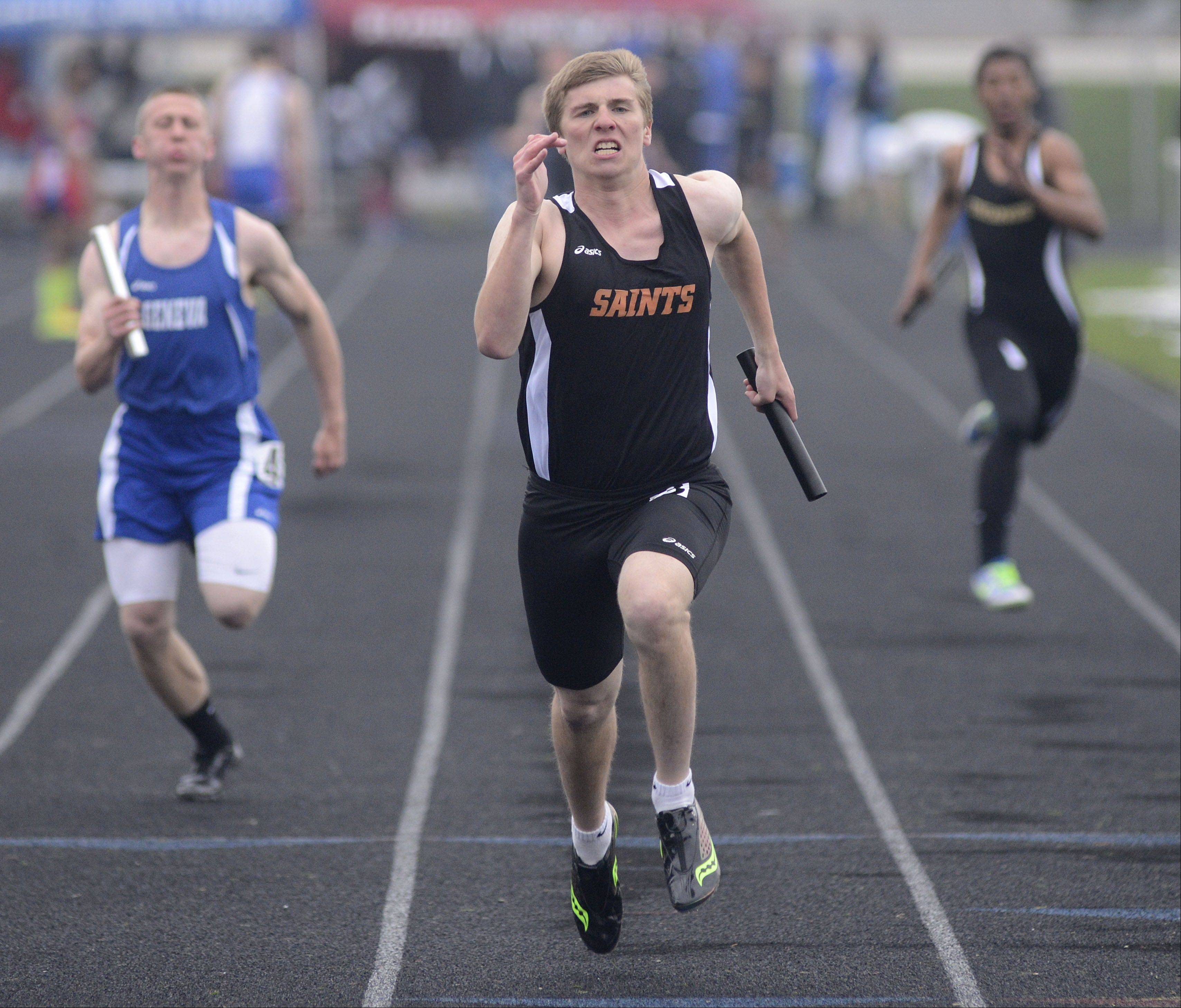 St. Charles East's Evan Connelly helps the Saints take first place in the first heat of the 4 x 100 meter relay at the Kane County boys track meet at Burlington Central on Friday.
