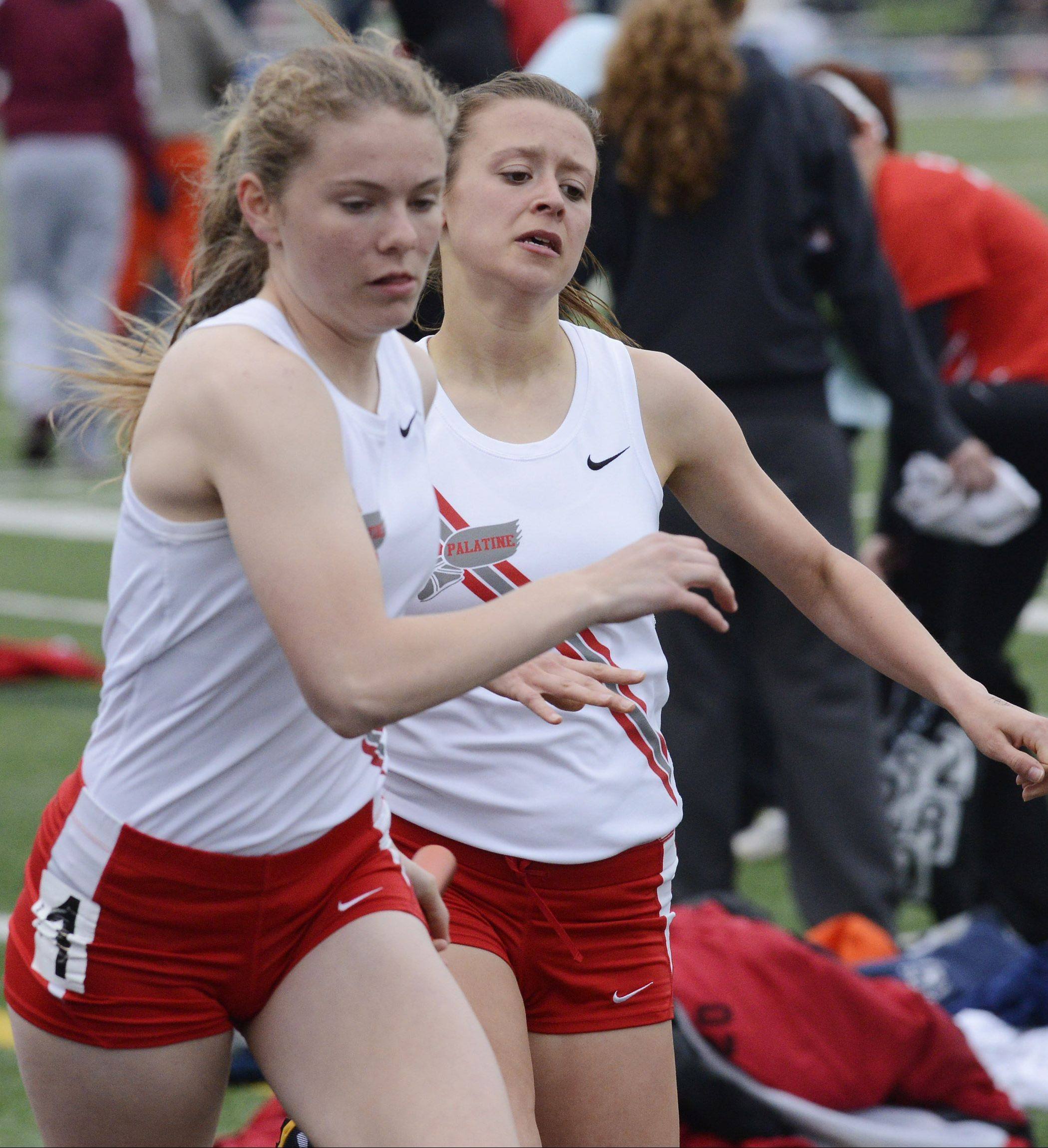 Palatine's Kara Burton, left, takes the baton from teammate Tess Wasowicz for the anchor leg of the 4 x 800-meter relay during the Mid-Suburban League girls track meet at Schaumburg on Friday.