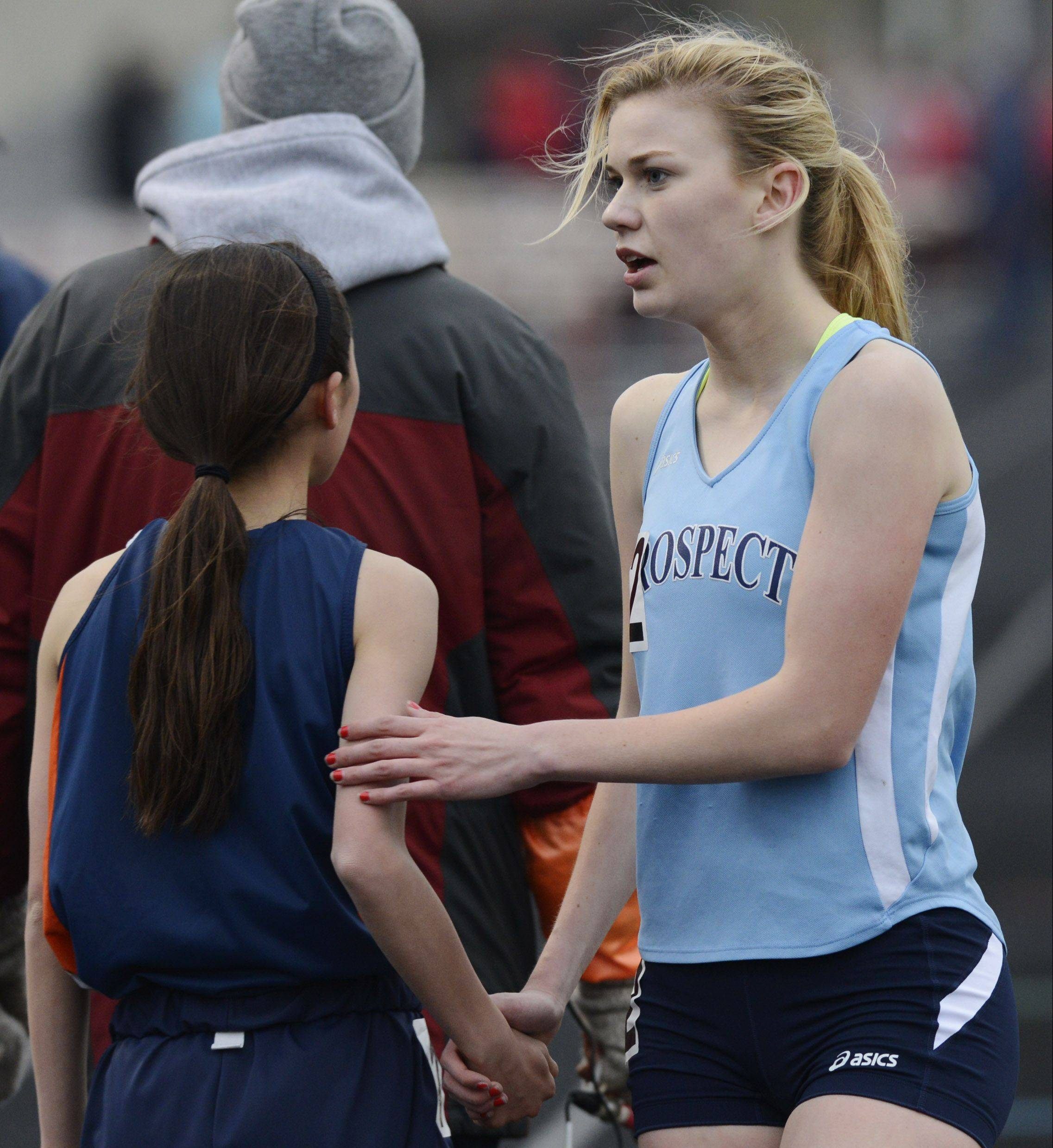 Prospect's Brooke Wolfe, right, who finished second in the 3,200-meter run, congratulates winner Kaitlyn Ko of Buffalo Grove during the Mid-Suburban League girls track meet at Schaumburg on Friday.