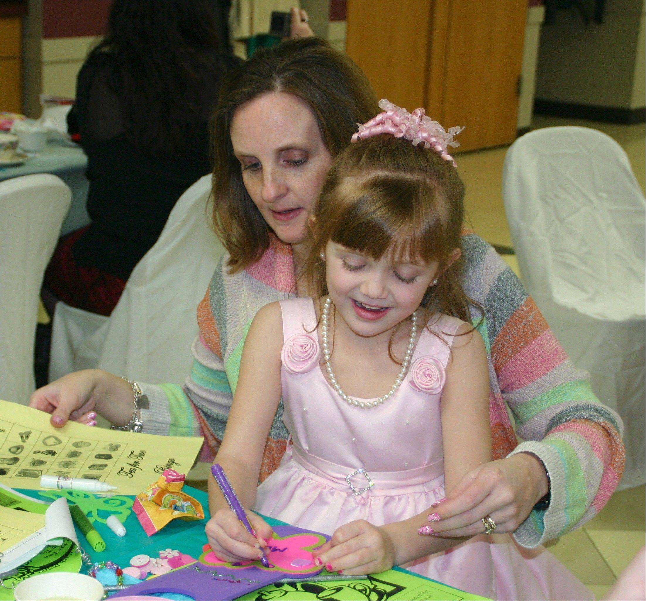 Mia Parcell and her mother make a craft at the 2013 Mother Daughter Tea at Prairie Lakes on April 13.