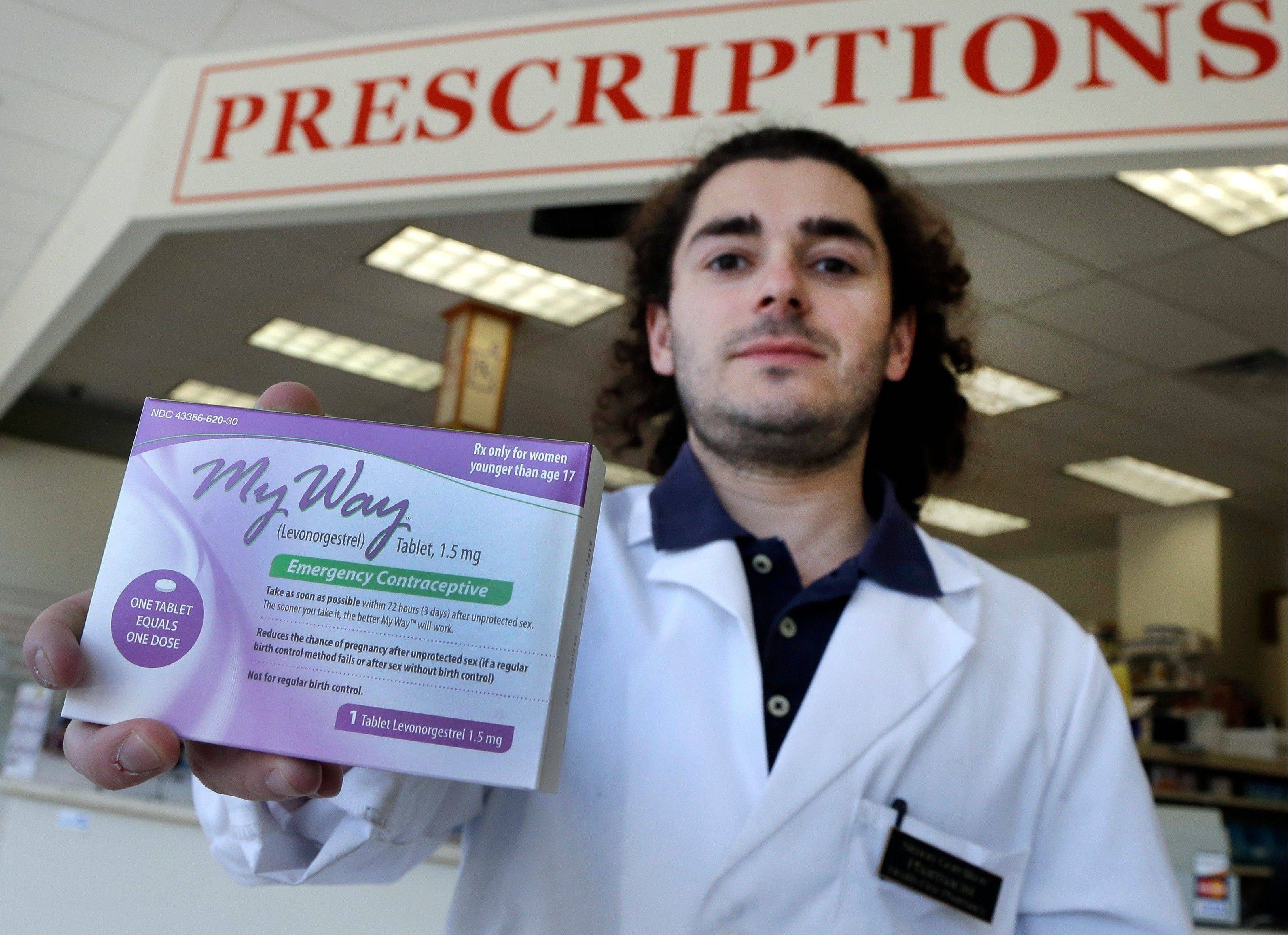 Pharmacist Simon Gorelikov holds a generic emergency contraceptive Thursday at the Health First Pharmacy in Boston.