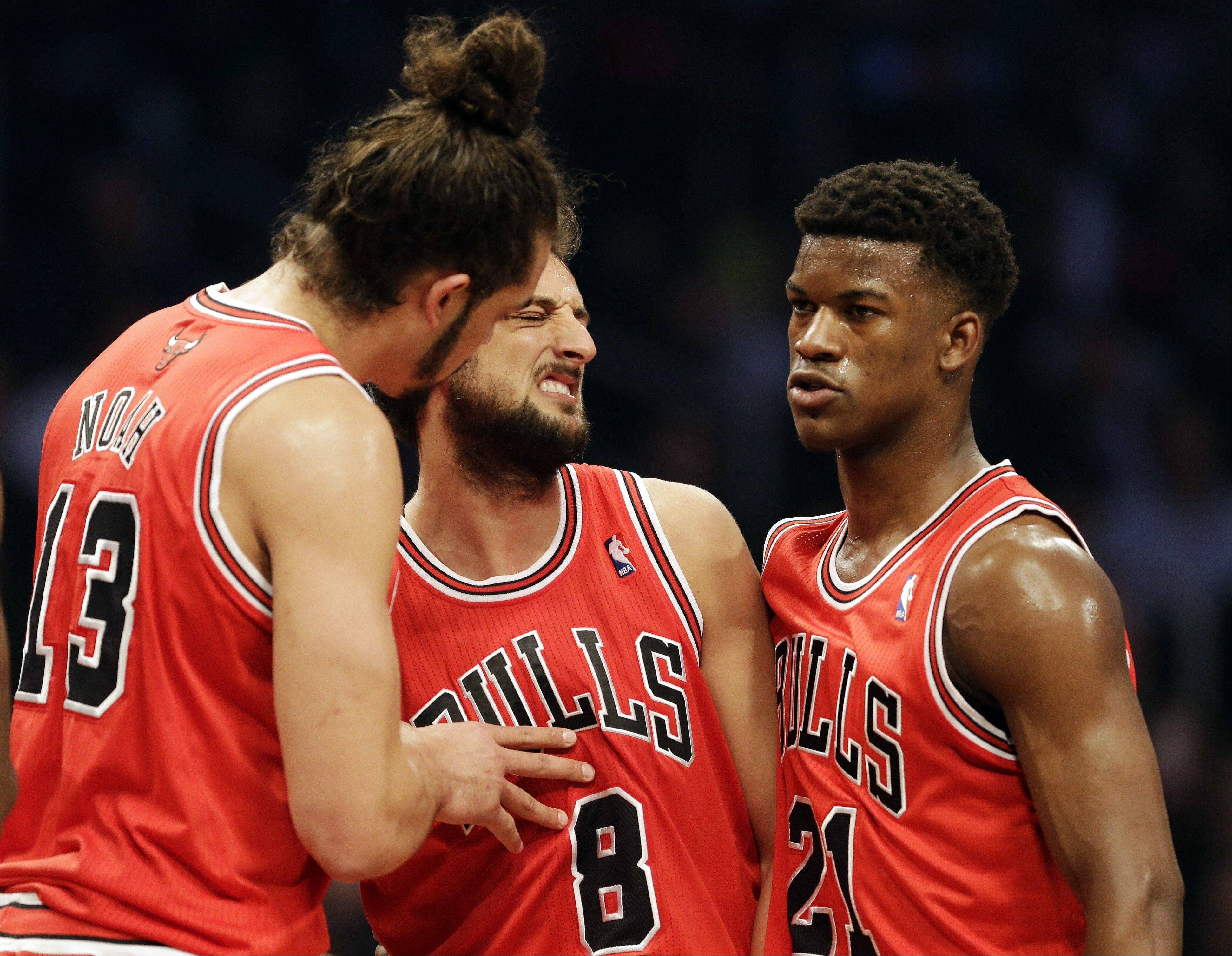 Marco Belinelli, center, reacts as teammates Joakim Noah, left, and Jimmy Butler talk to him during the first half in Game 7 of their first-round NBA basketball playoff series against the Brooklyn Nets in New York, Saturday, May 4, 2013.