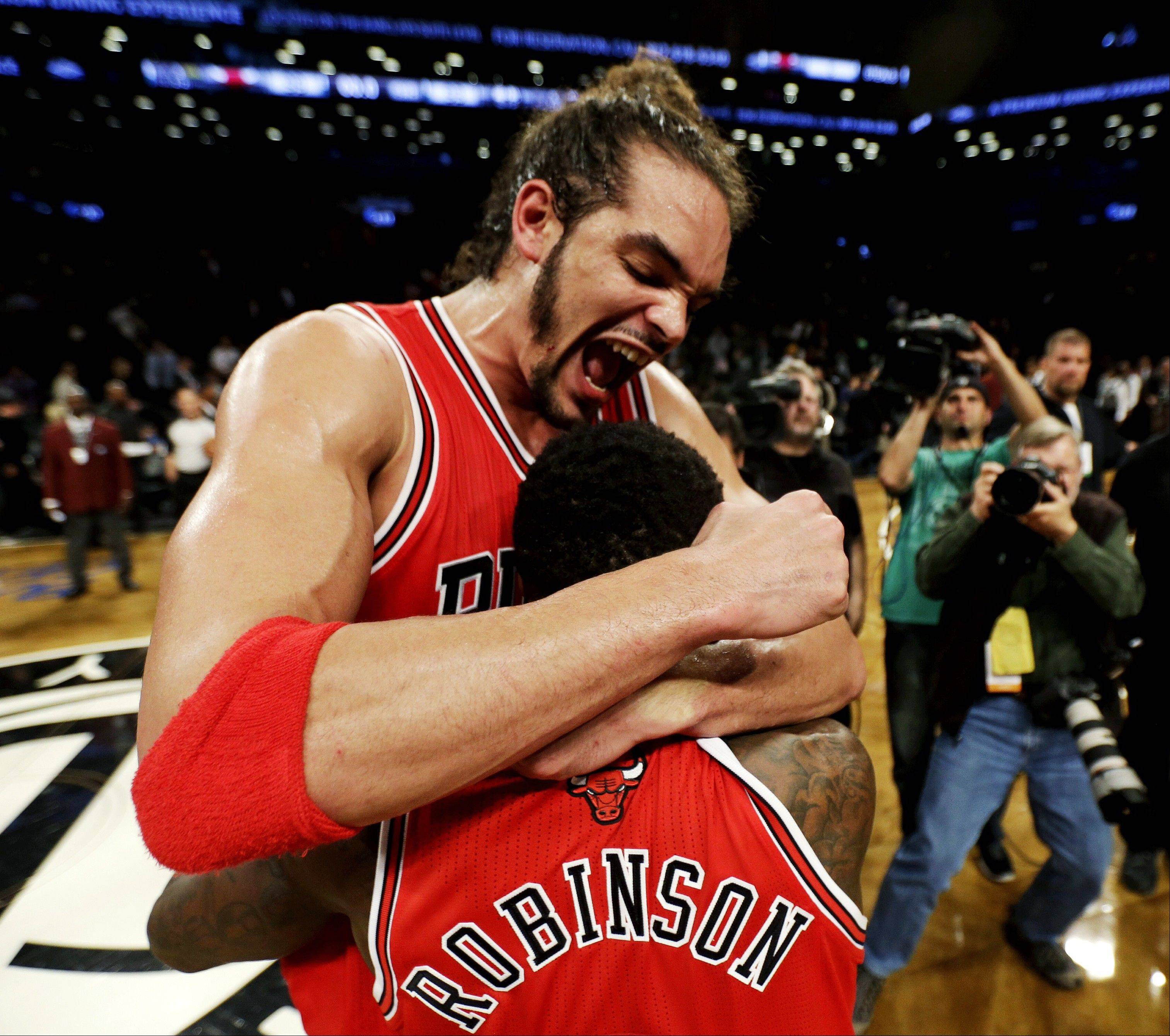 Chicago Bulls' Joakim Noah, top, celebrates with teammate Nate Robinson after defeating the Brooklyn Nets 99-93 in Game 7 of their first-round NBA basketball playoff series in New York, Saturday, May 4, 2013. The Bulls won the series to advance to a second-round series against the Miami Heat beginning Monday. (AP Photo/Julio Cortez)