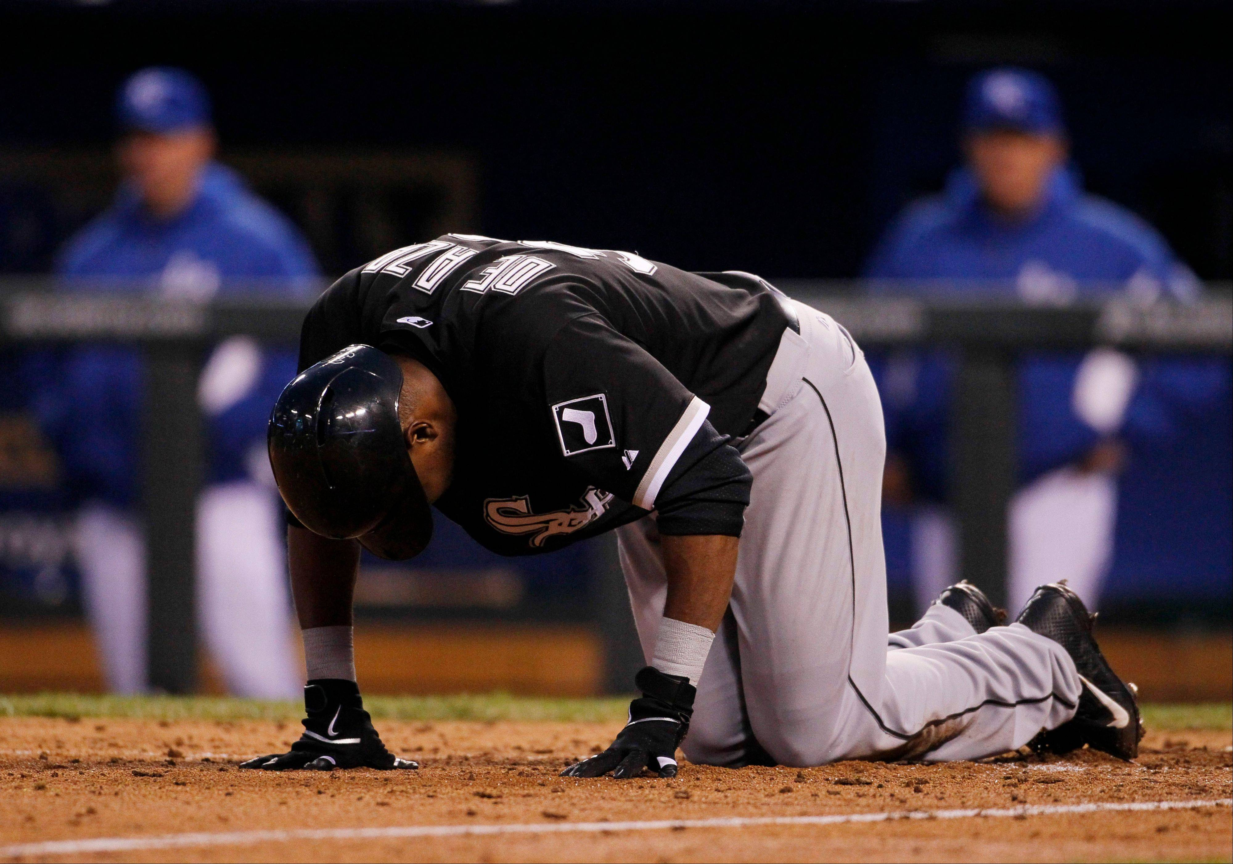 Chicago White Sox batter Alejandro De Aza falls to the ground after fouling off the ball on to his leg in the seventh inning against the Kansas City Royals at Kauffman Stadium in Kansas City, Mo.