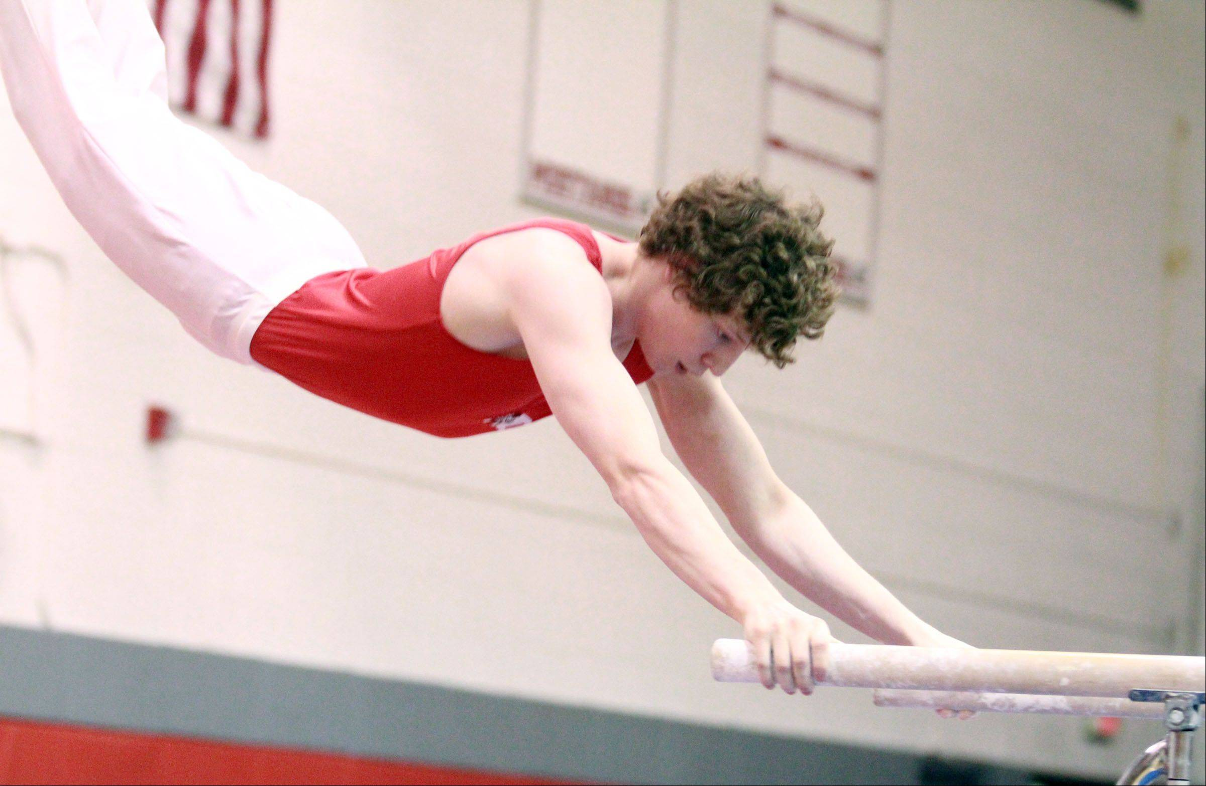 Mundelein's Jacob Petri competes on the parallel bars at the Mundelein boys gymnastics sectional on Saturday.