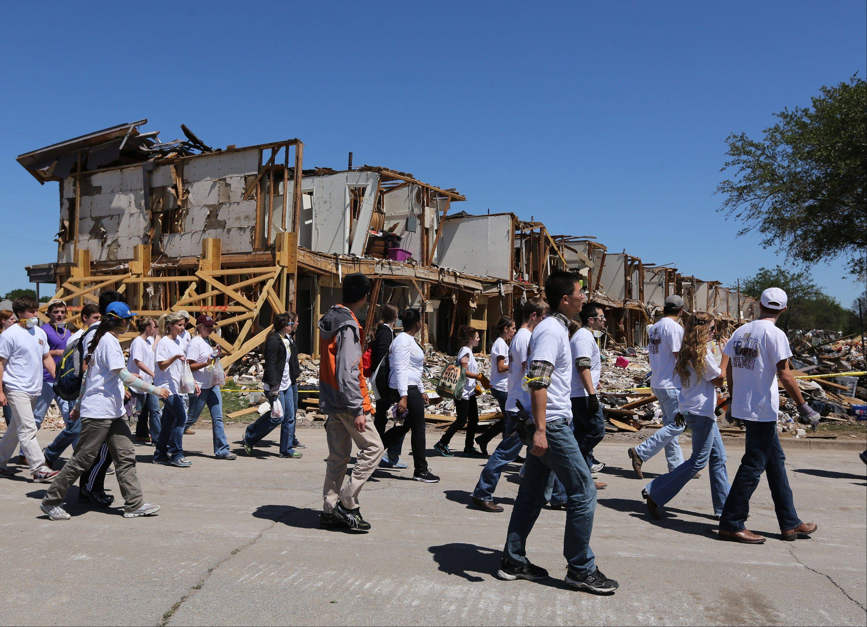 Texas A&M students walk past an apartment complex Saturday in West, Texas, that was damaged due to the explosion at a fertilizer plant on April 17. The plant that exploded had only $1 million in liability coverage, lawyers said Saturday.