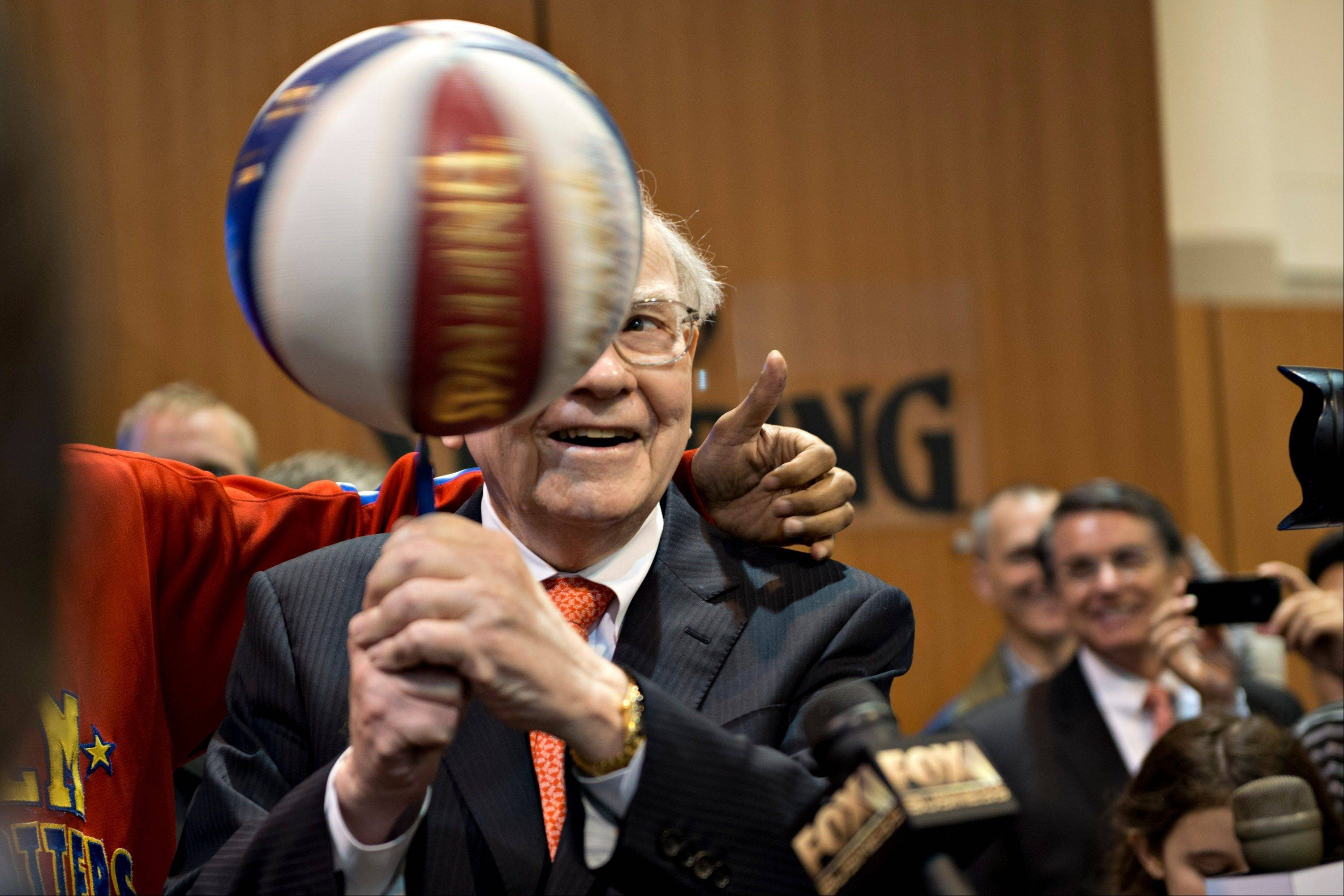 Warren Buffett, chairman and chief executive officer of Berkshire Hathaway Inc., spins a basketball on a pen Saturday as he stands with a member of the Harlem Globetrotters during a tour of the exhibition floor prior to the start of the Berkshire shareholders meeting in Omaha, Nebraska.
