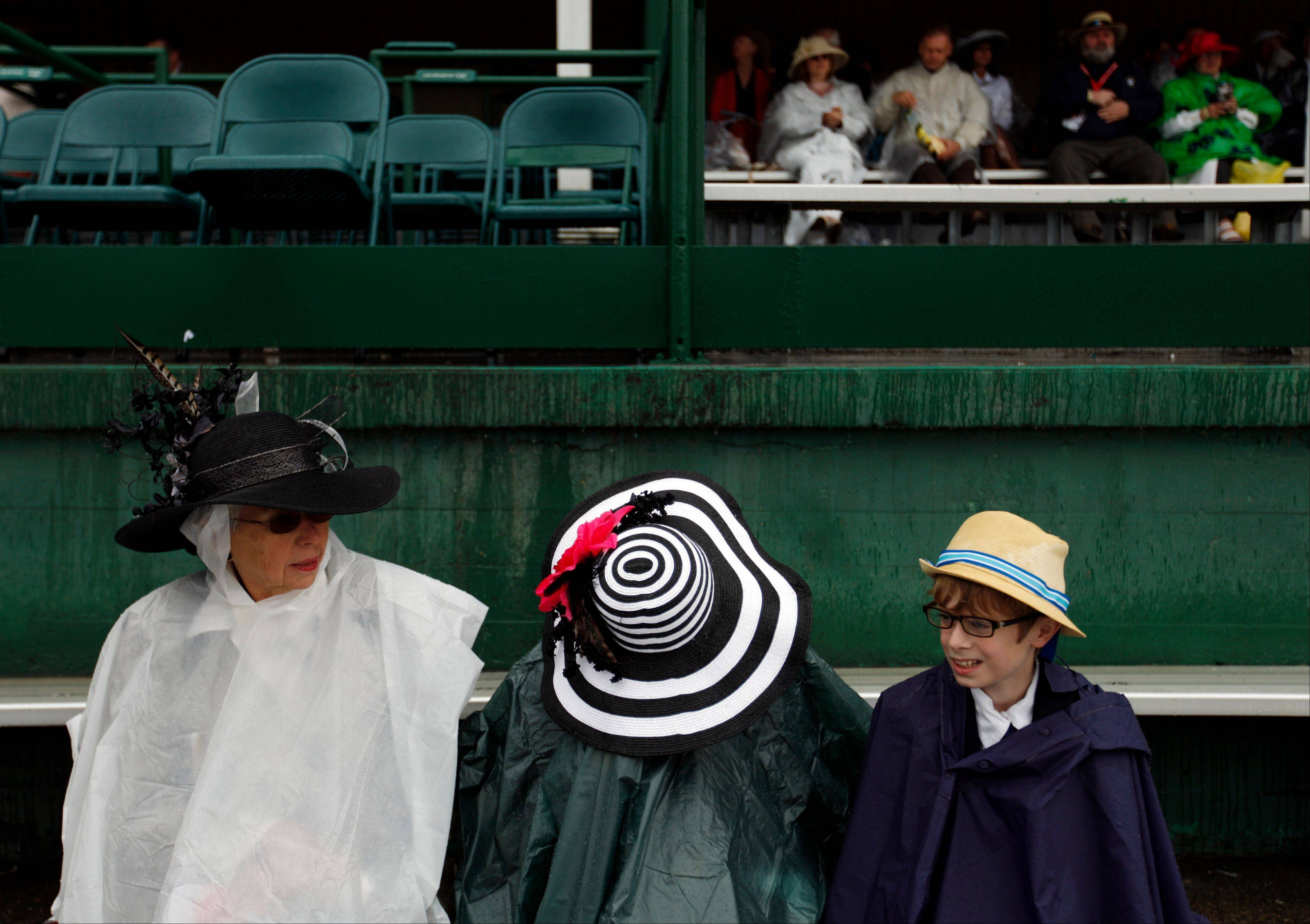 From left, Donna Osborne, from Clemens, N.C., waits in the rain with Annie and Oz before the 139th Kentucky Derby.