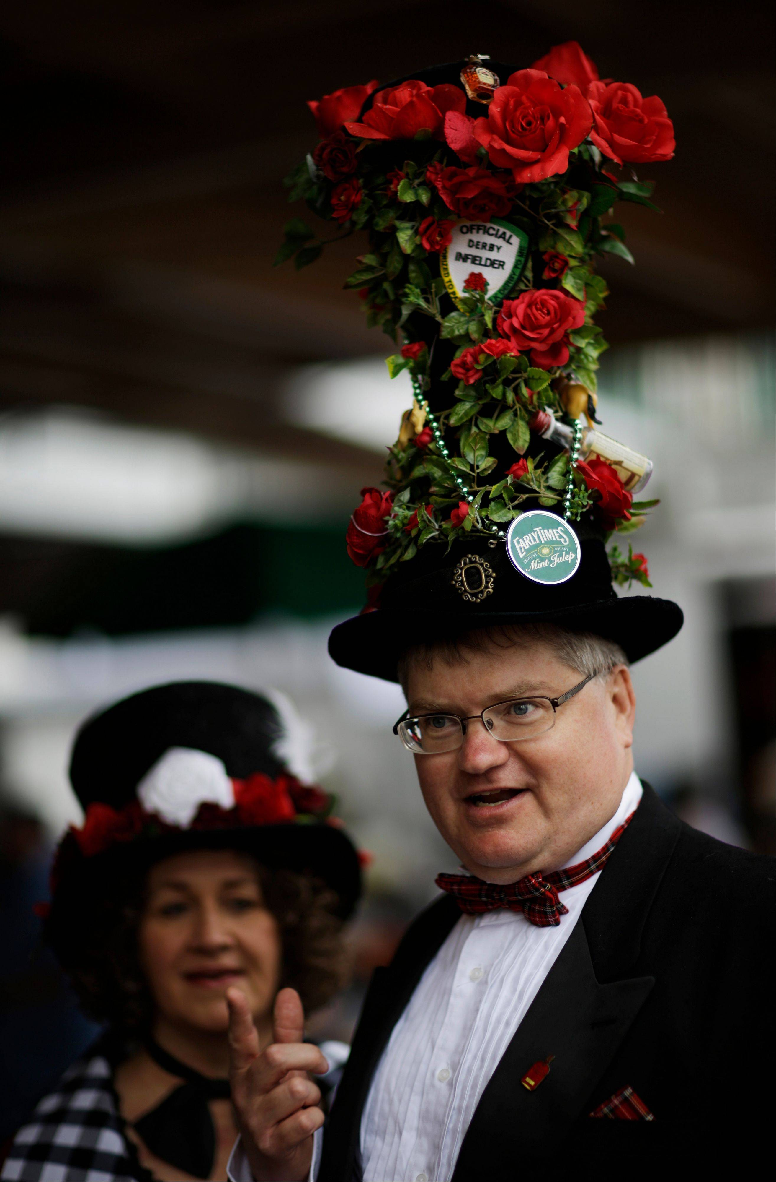 Tim Rask, from Iowa City, Iowa, shows off his fancy hat with Theresa Klingenberg before the running of the 139th Kentucky Derby at Churchill Downs Saturday.