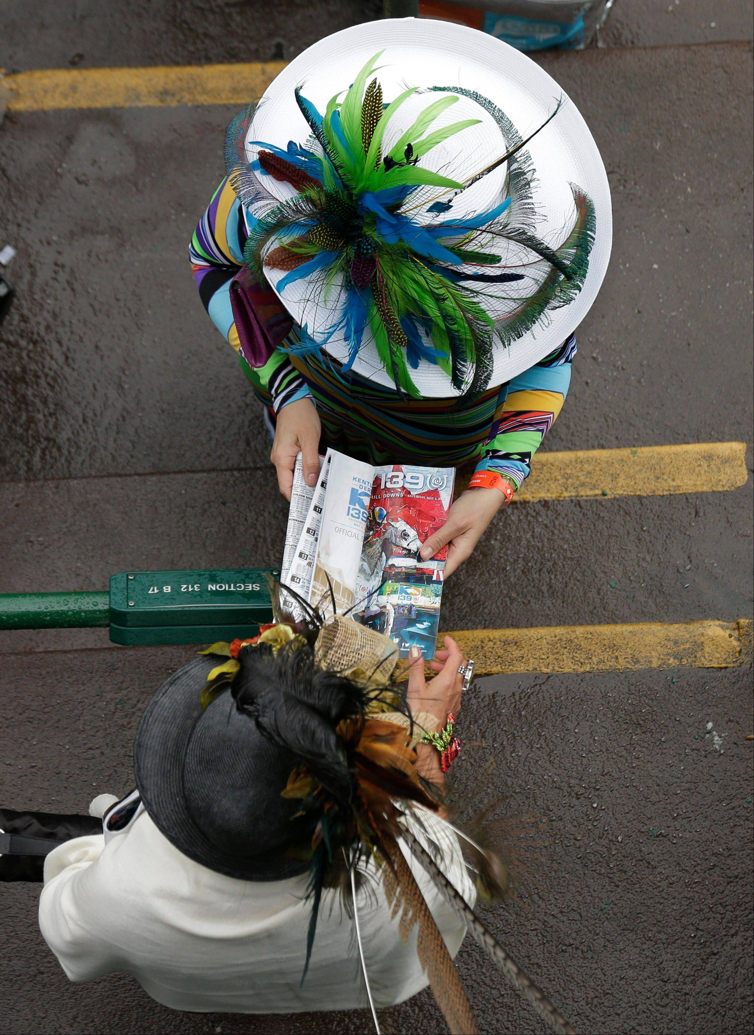 Race goers examine the racing program before the 139th Kentucky Derby.