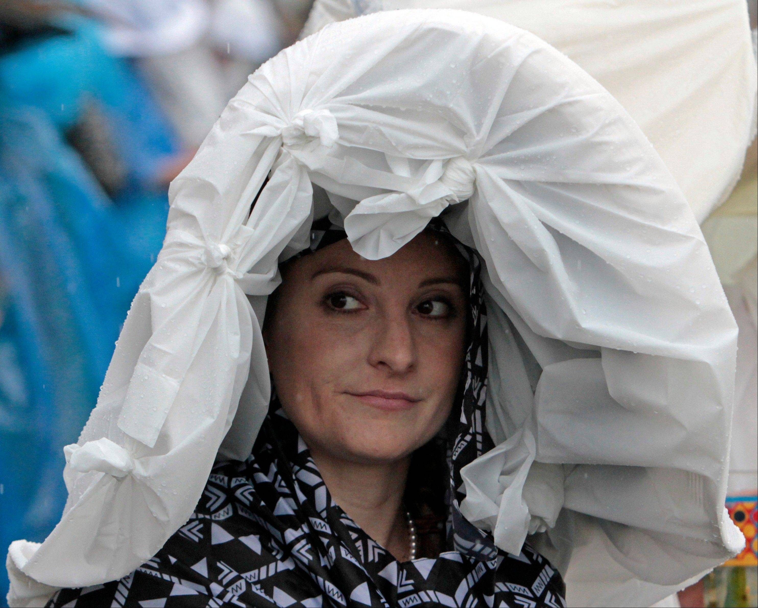 Jennifer Parod, Tucson, Az., looks out from her plastic covered hat before the 139th Kentucky Derby.