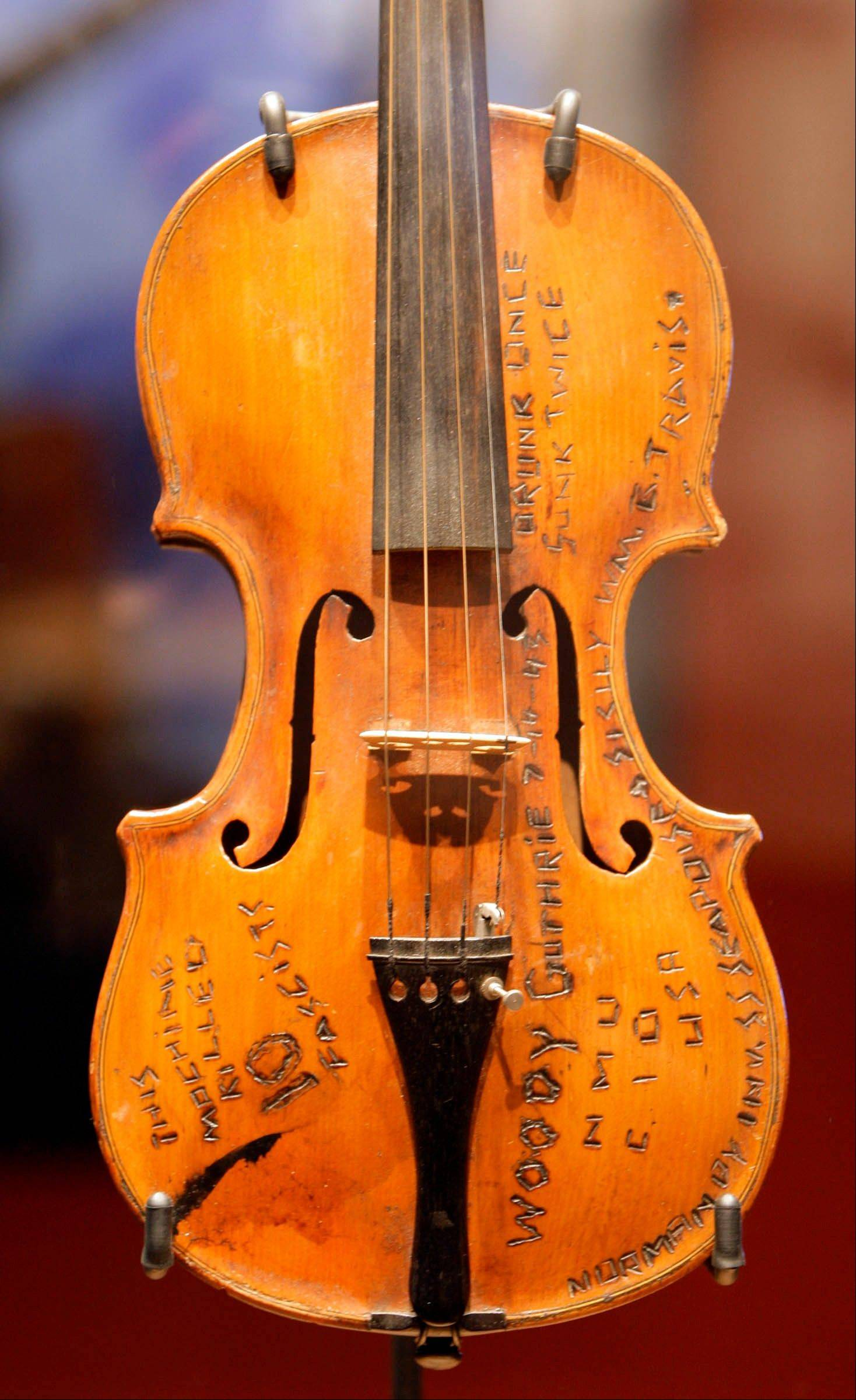Woody Guthrie's violin, carved and woodburned with references to the time, is on display at the Woody Guthrie Center.