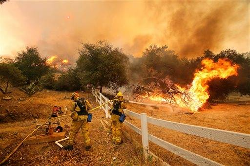 Firefighters from Stockton, Calif., put out flames off of Hidden Valley Rd. while fighting a wildfire, Friday, May 3, 2013 in Hidden Valley, Calif. A huge Southern California wildfire burned through coastal wilderness to the beach on Friday then stormed back through canyons toward inland neighborhoods when winds reversed direction.