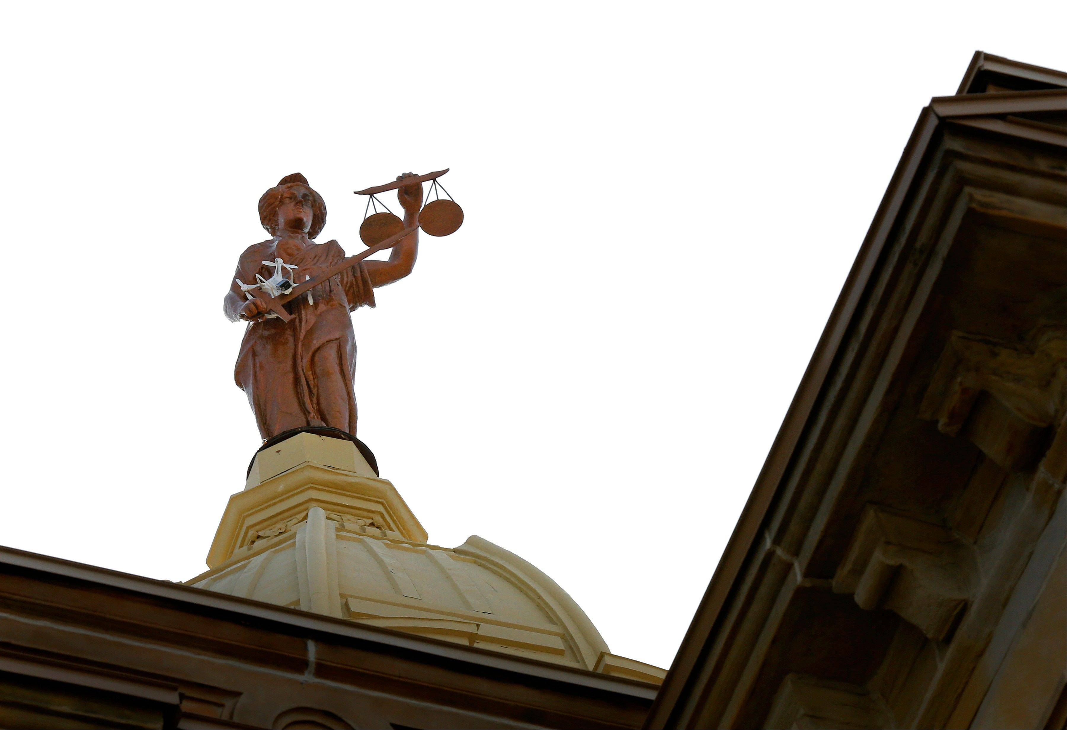 Terry Cline's drone camera sits stuck in the arm of the Lady Justice statue Thursday atop the Marion County Courthouse. The remote-control helicopter got stuck while he was filming a project.