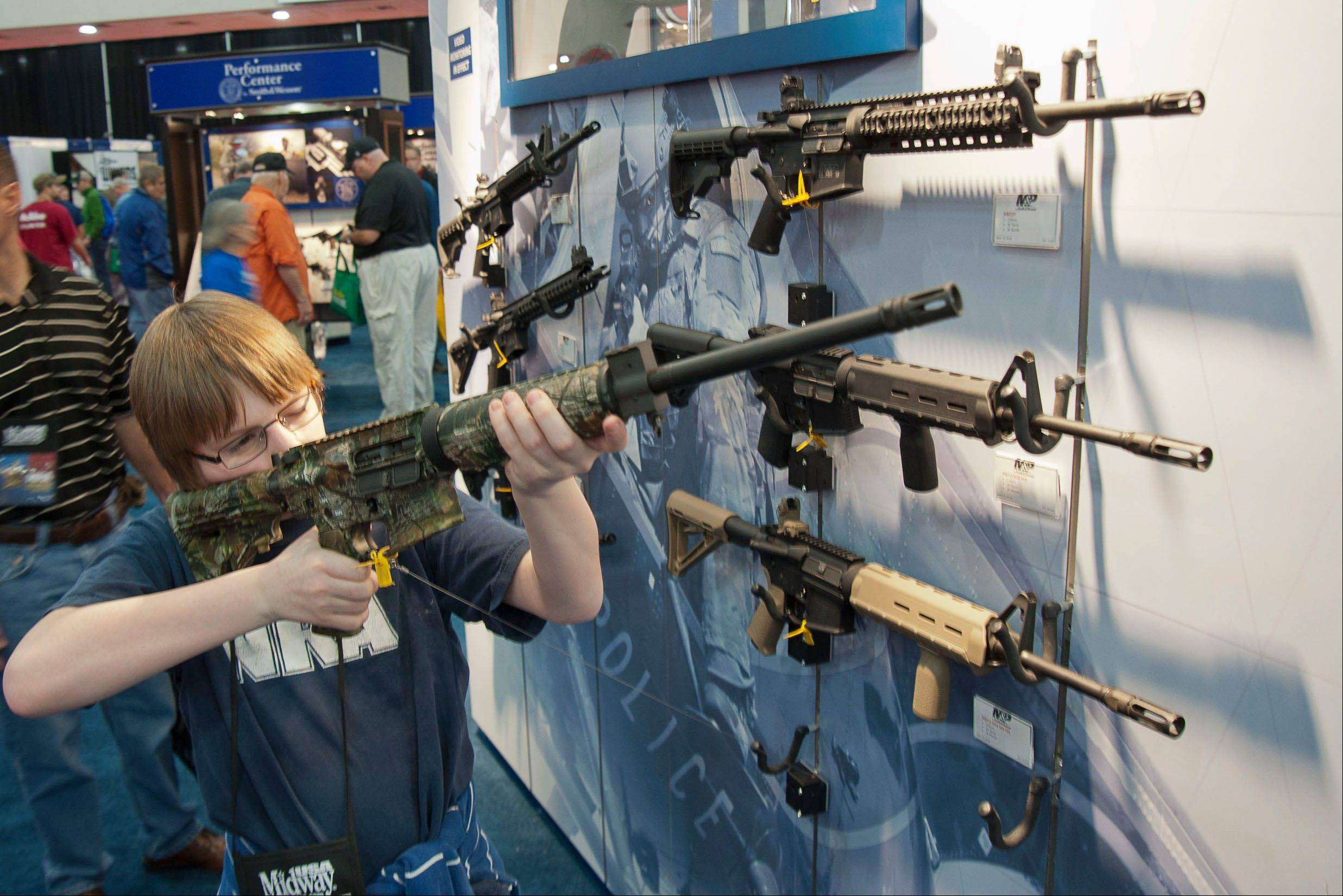 A young man who chose not to give his name sizes-up an assault style rifle Friday during the National Rifle Association's annual convention.