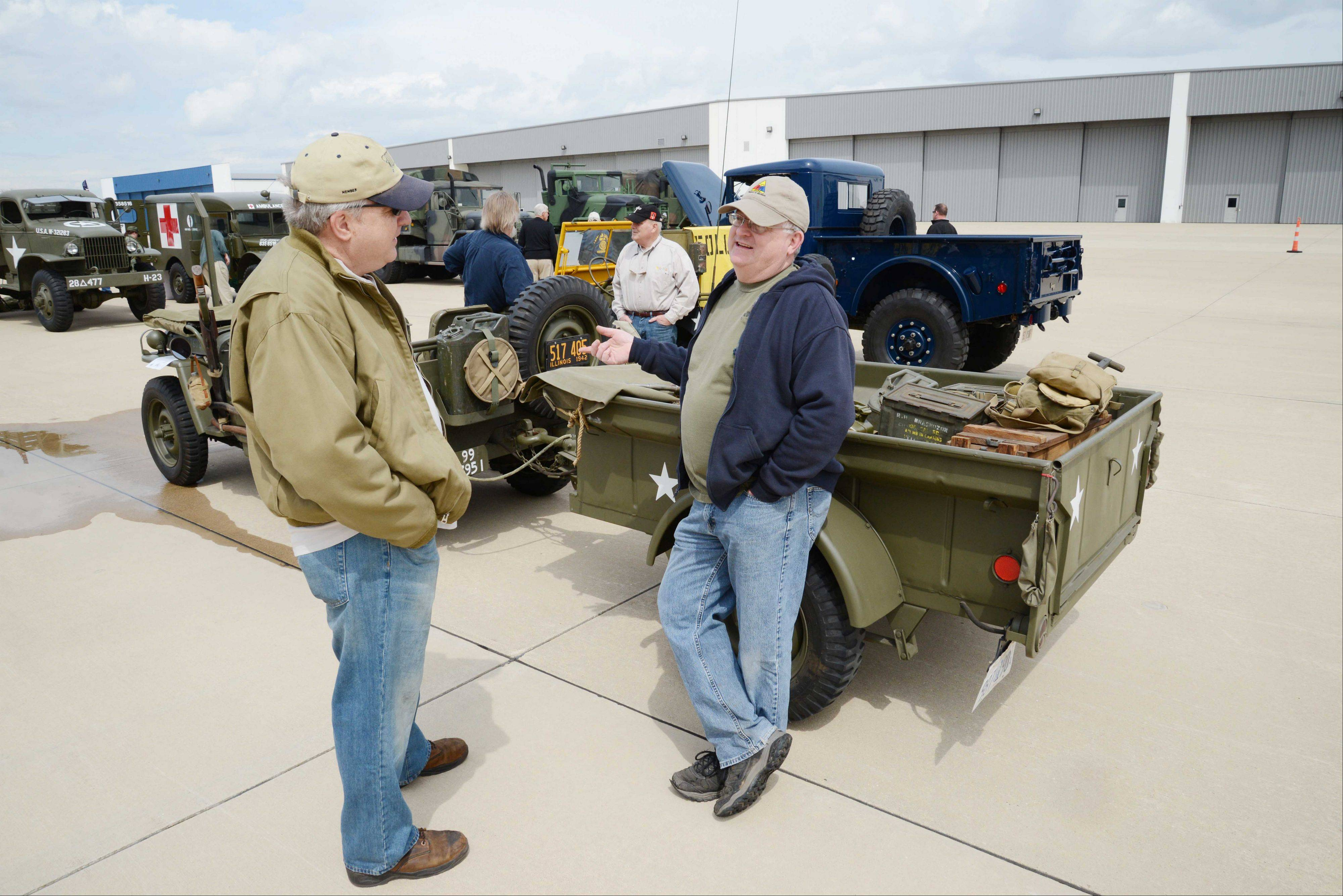 Tom Lachowiez of Downers Grove leans against a 1942 Ford GPW as he talks with Steve Earl of Geneva left, during a fundraiser for Honor Flight Chicago Saturday at DuPage Airport. The event, hosted by the DuPage Veterans Foundation, included lunch with veterans.