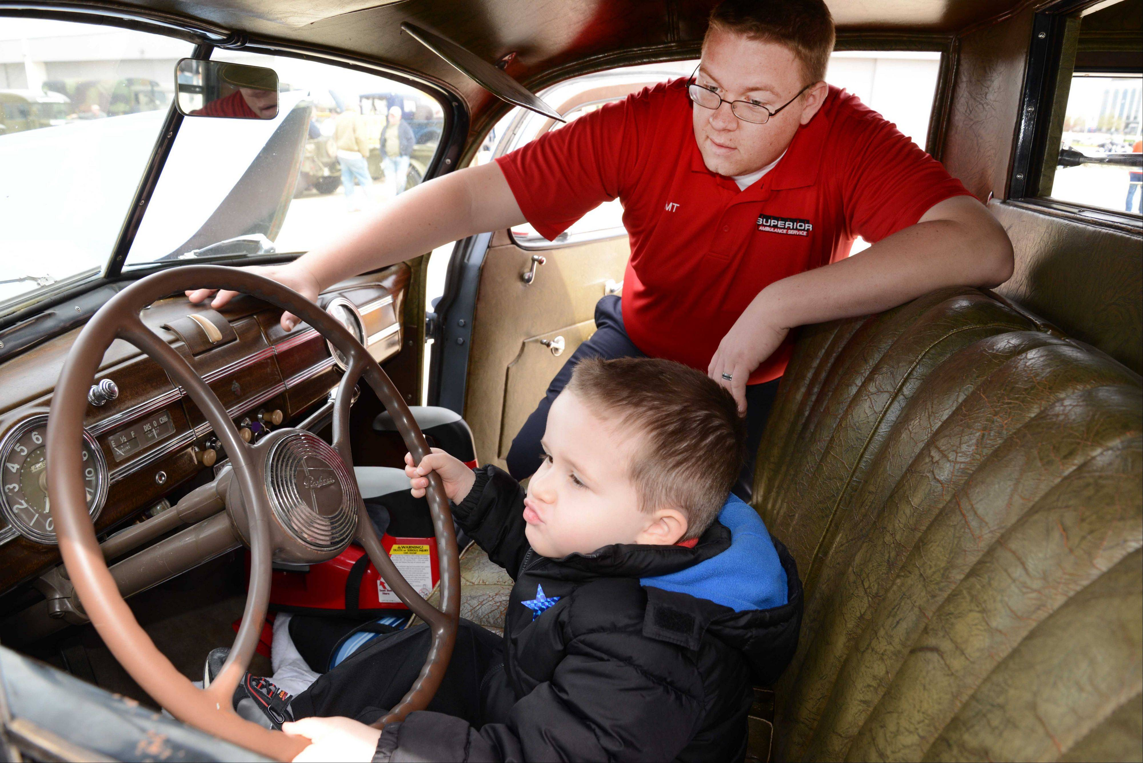 Robert Wangles and his stepson Jacob Valade, 3, of Crystal Lake, sit in a 1940 Packard Ambulance used during wartime during a fundraiser for Honor Flight Chicago Saturday at DuPage Airport. The event, hosted by the DuPage Veterans Foundation, included lunch with veterans.