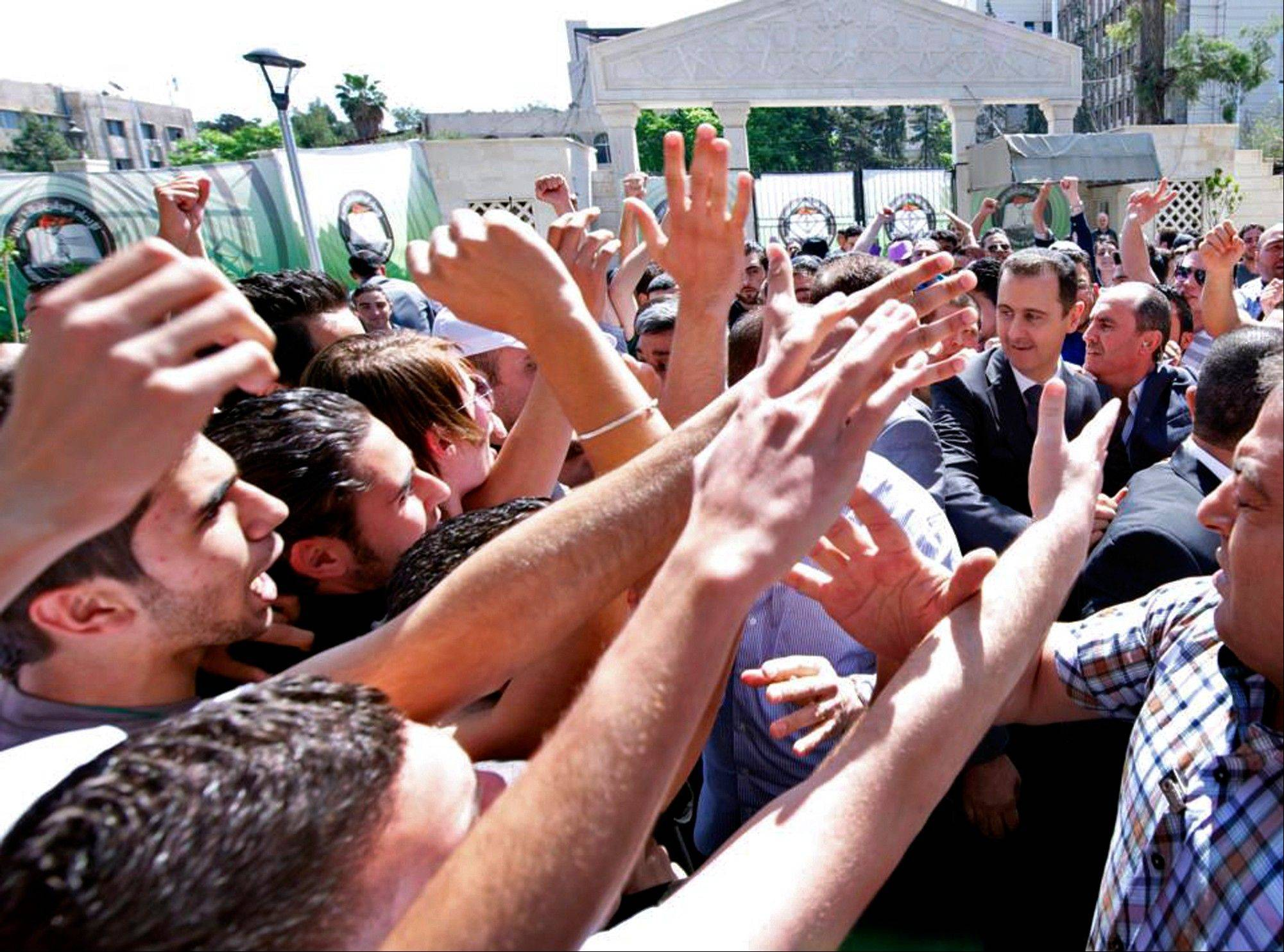"This photo, released on the official Facebook page of Syrian President Bashar Assad, shows Syrian president Bashar Assad, right, surrounded by bodyguards as young people, wave at him during the inauguration ceremony on Saturday of a statue dedicated to ""martyrs"" from Syrian universities who died in the country's two-year-old uprising and civil war, in Damascus."