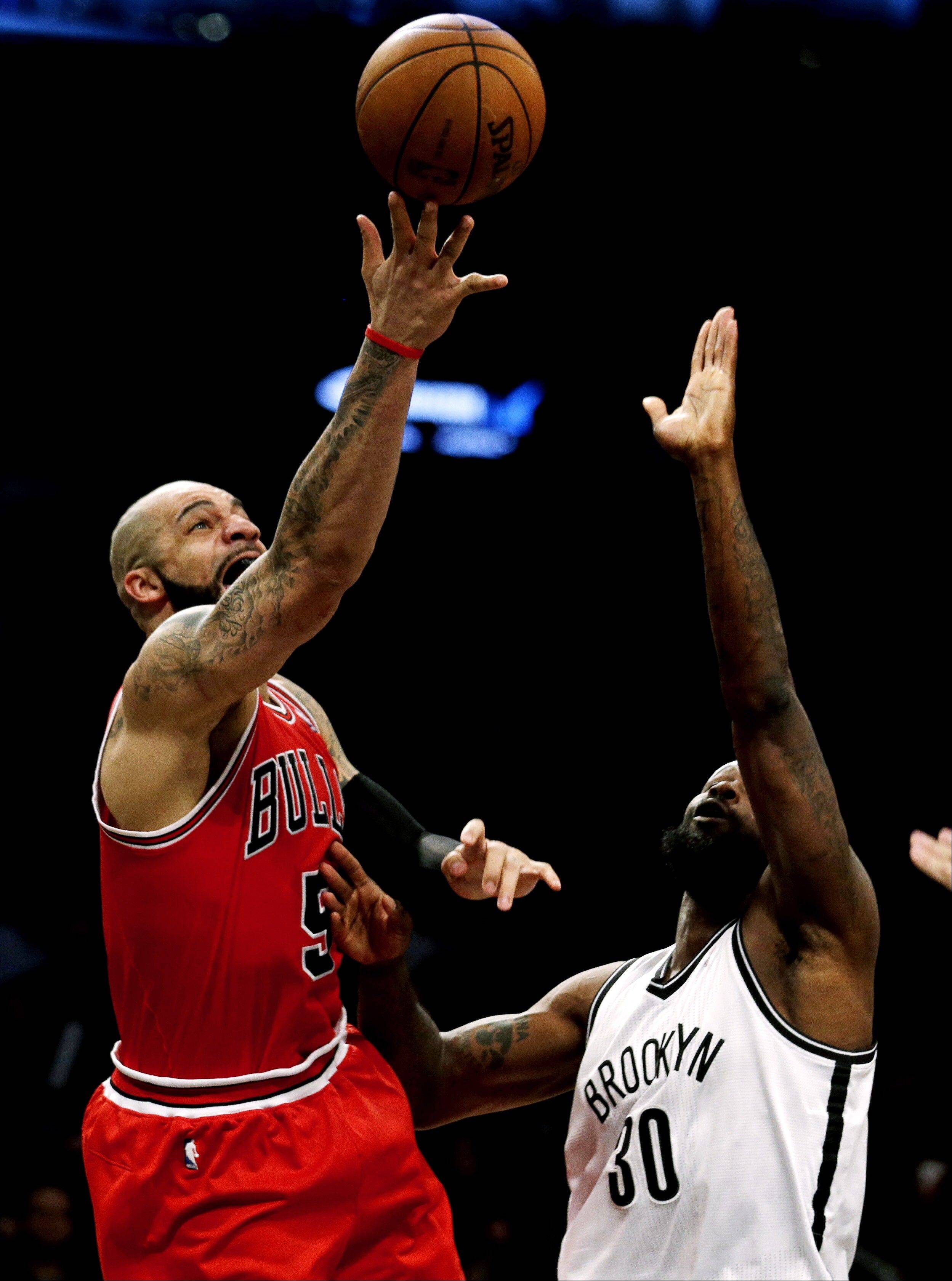 Chicago Bulls forward Carlos Boozer, left, shoots against Brooklyn Nets' Reggie Evans during the second half in Game 7 of their first-round NBA basketball playoff series in New York, Saturday, May 4, 2013.