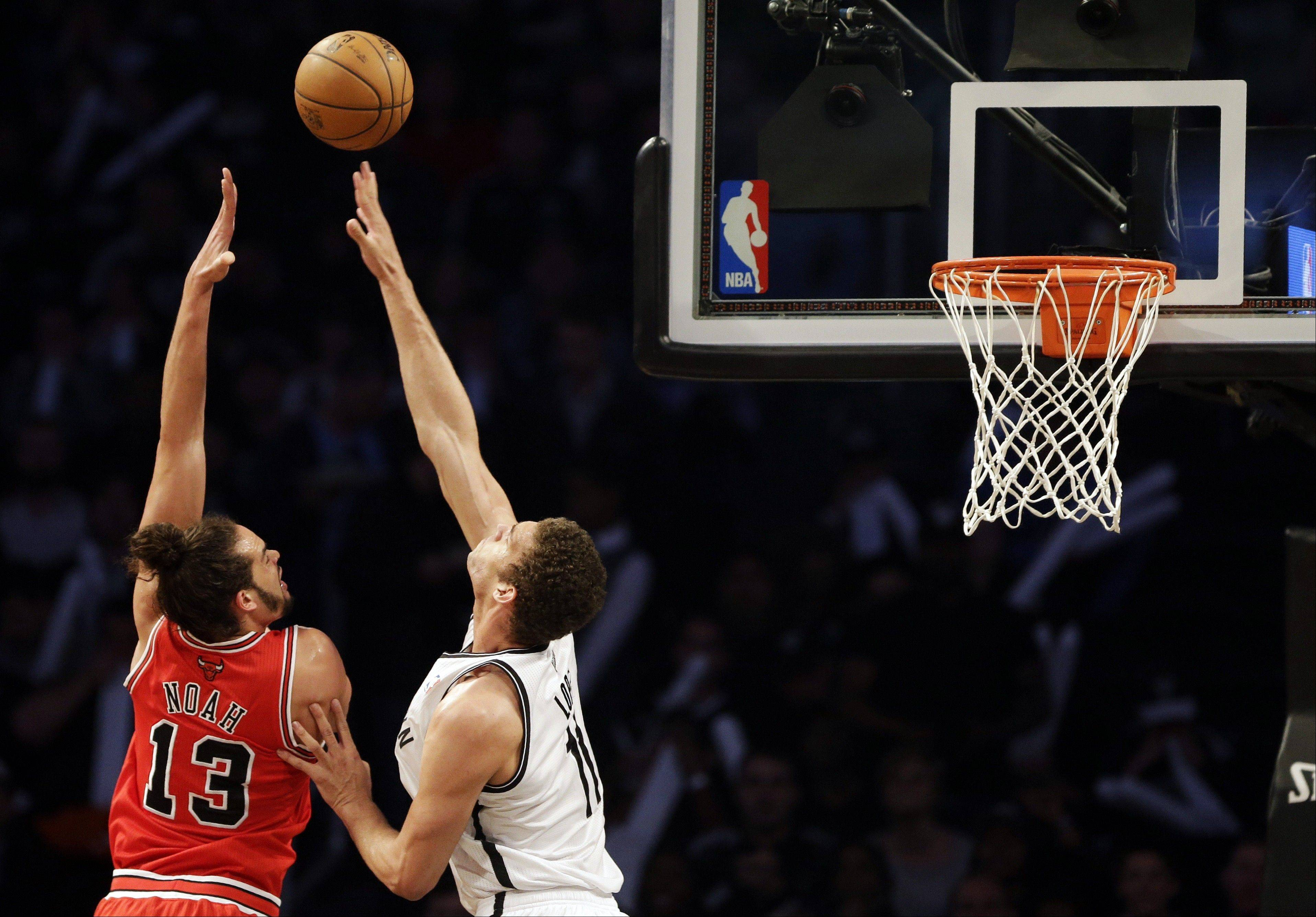 Chicago Bulls center Joakim Noah, left, shoots against Brooklyn Nets center Brook Lopez during the first half in Game 7 of their first-round NBA basketball playoff series in New York, Saturday, May 4, 2013.