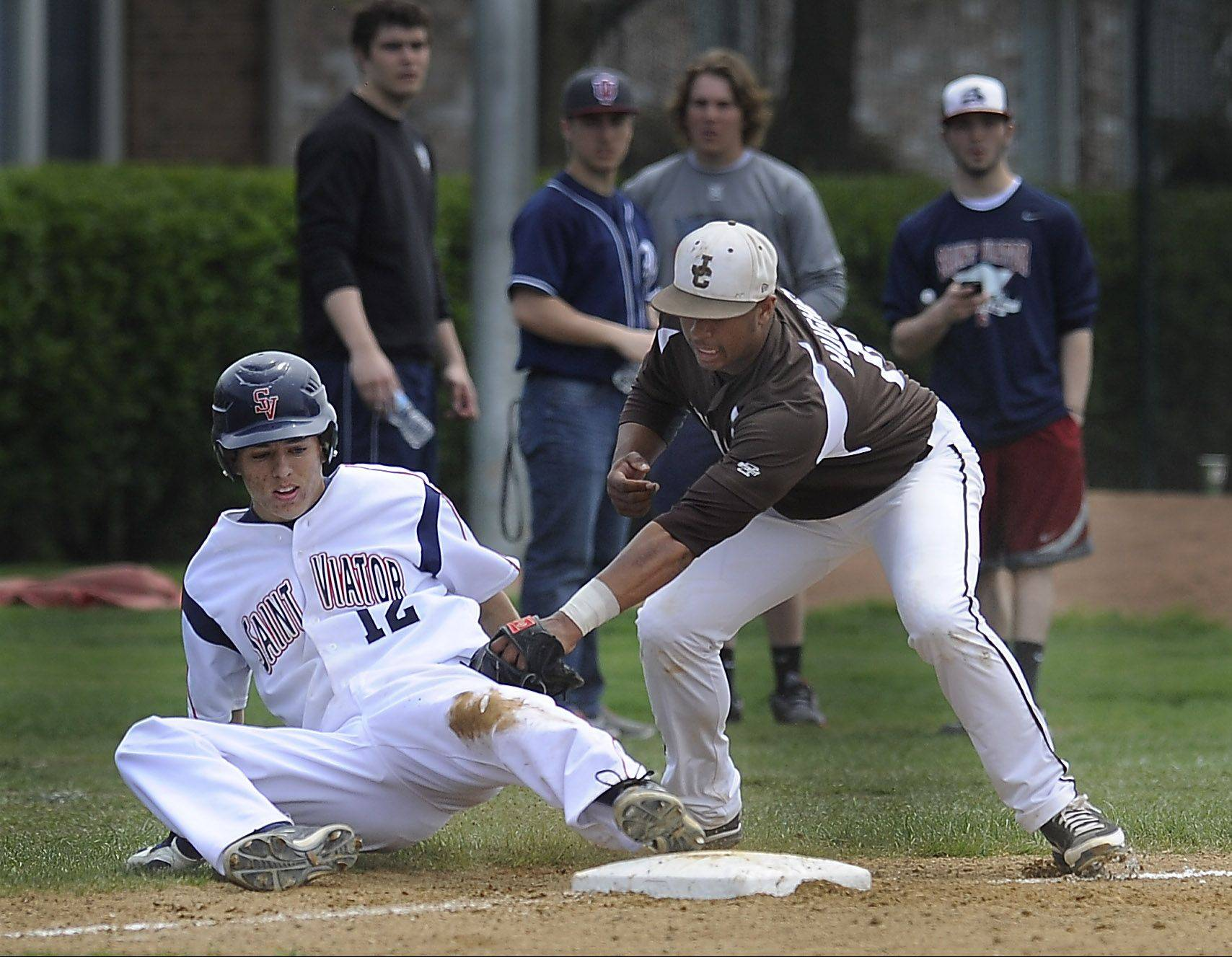 St. Viator's Andrew Ferrante is called out at third base in the bottom of the third inning as the tag is applied by Joliet Catholic's Ira Hughes in game one of doubleheader action at St. Viator on Saturday.