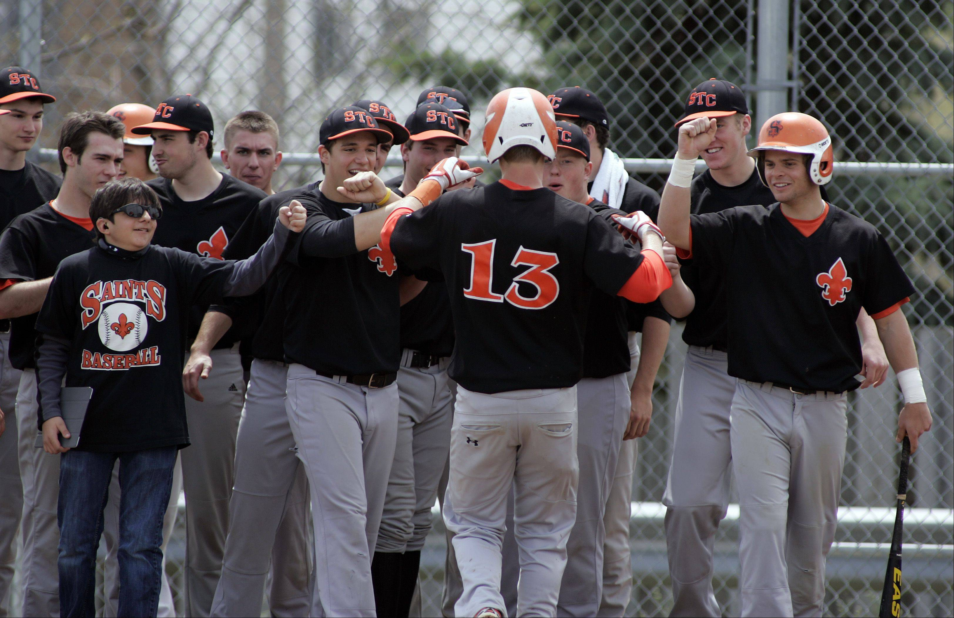 St. Charles East's Isaac Nimick (13) is greeted at the plate after knocking one out of the park during baseball action Saturday at Streamwood.