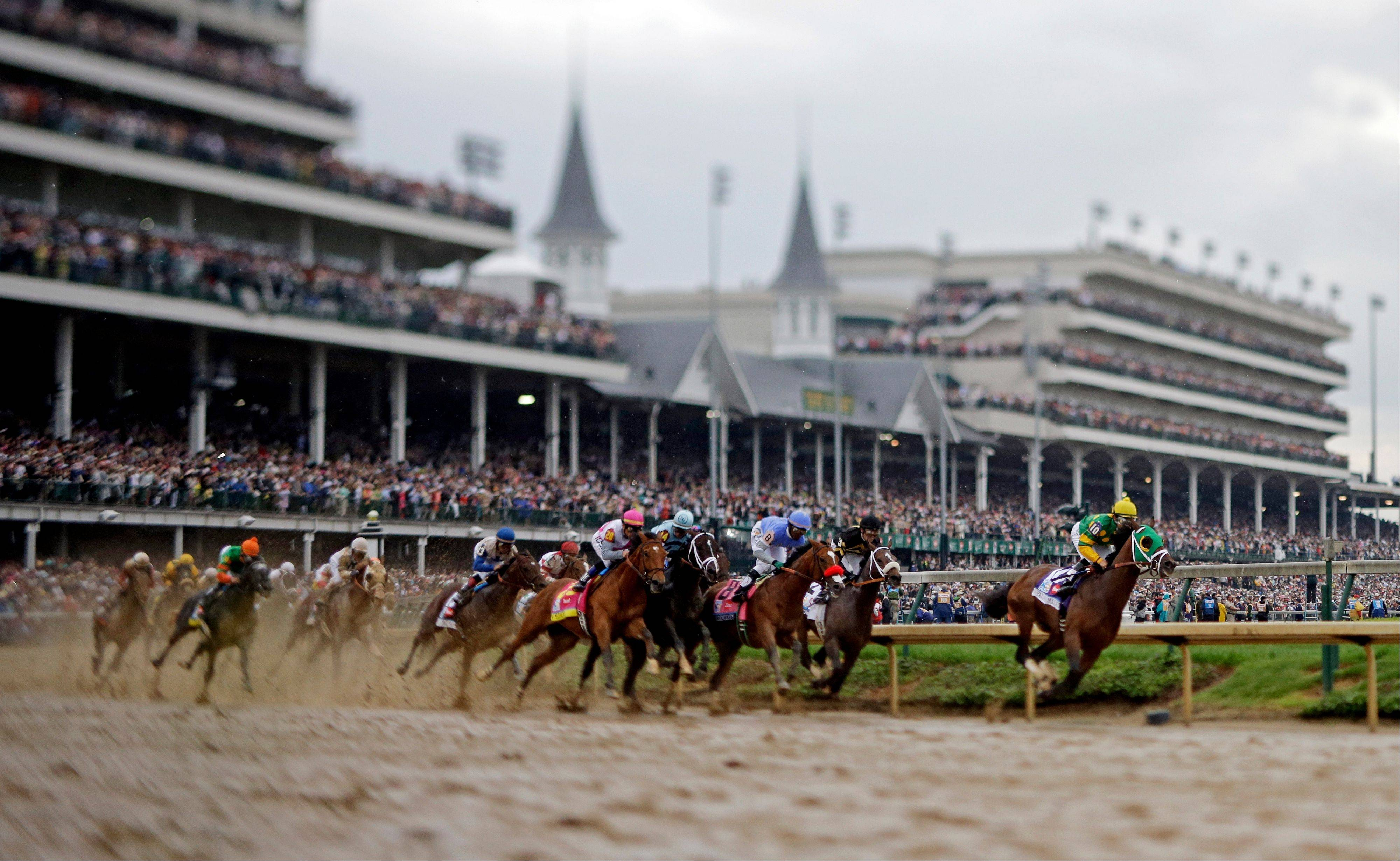 In this image made with a specialty lens, horses make their way around turn one during the 139th Kentucky Derby at Churchill Downs Saturday, May 4, 2013, in Louisville, Ky.