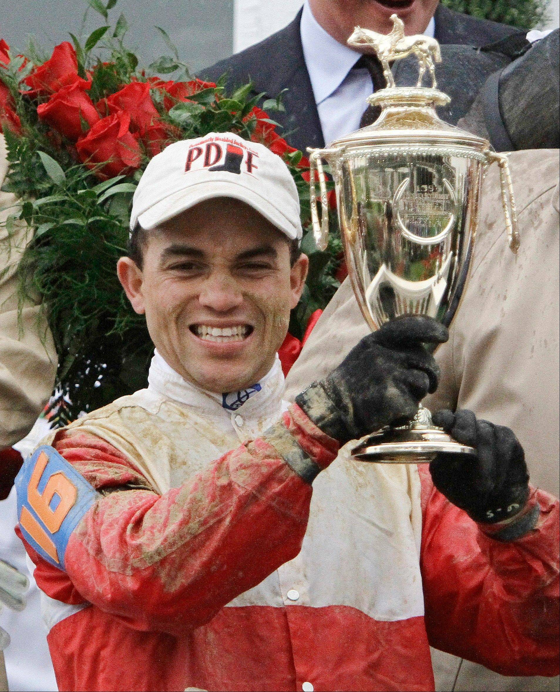 Joel Rosario holds the trophy after riding Orb to victory in the 139th Kentucky Derby at Churchill Downs Saturday, May 4, 2013, in Louisville, Ky.