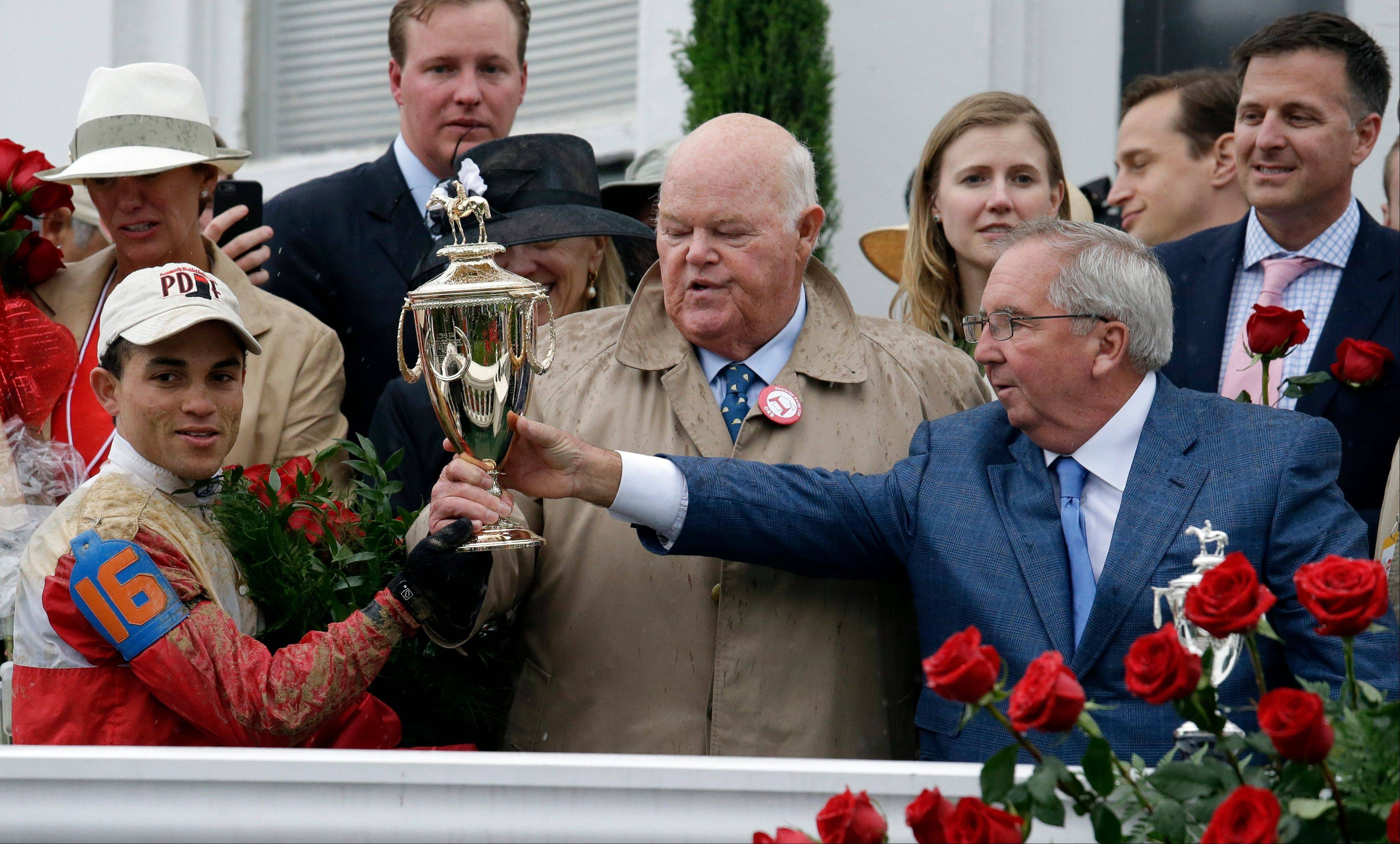Orb jockey Joel Rosario, left, trainer Claude McGaughey, right, and owner Ogden Phipps celebrate after winning the 139th Kentucky Derby at Churchill Downs Saturday, May 4, 2013, in Louisville, Ky.
