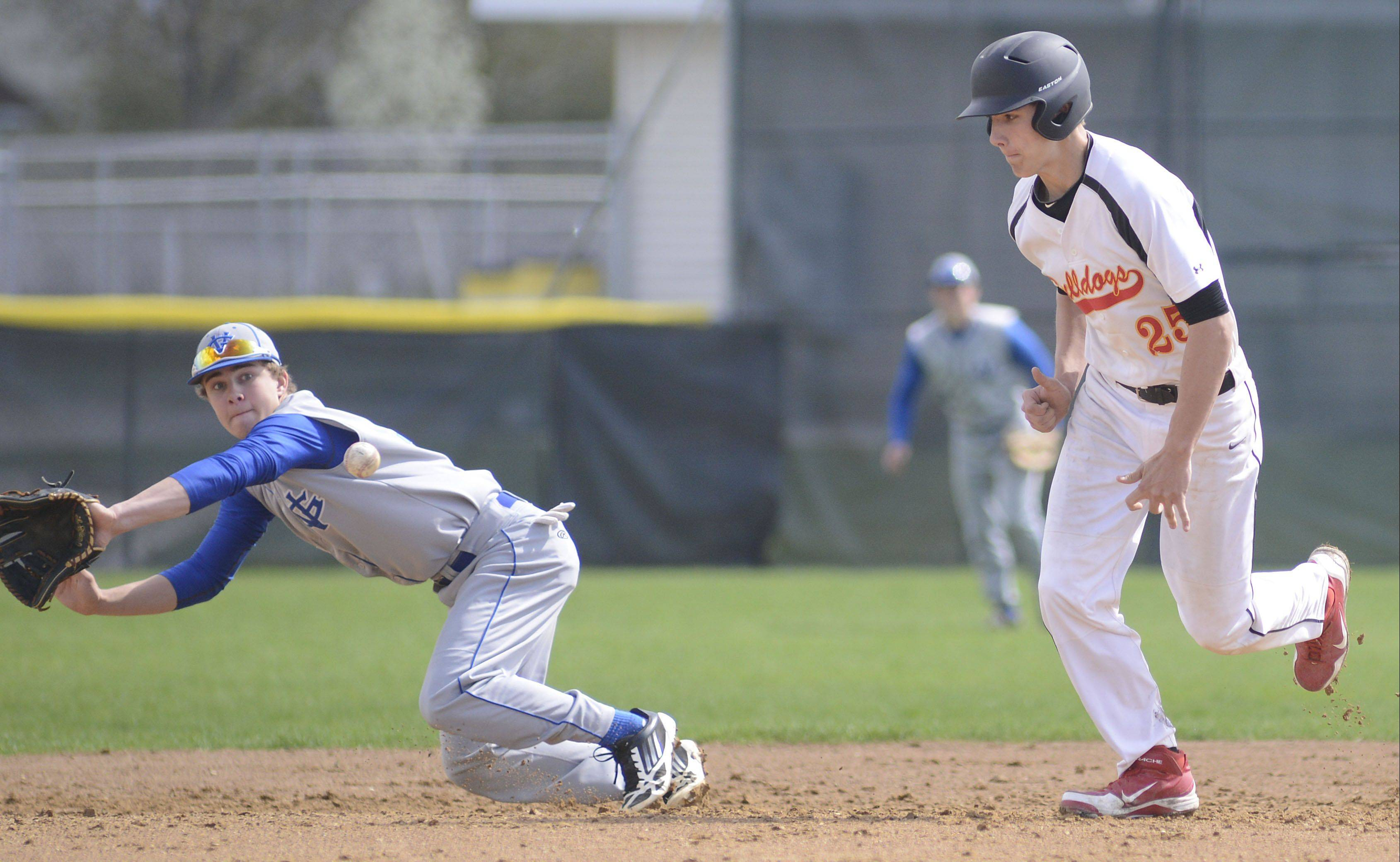 Geneva's Nick Derr dives for the ball as Batavia's Jordan Zwart takes off for third base in the second inning on Saturday.