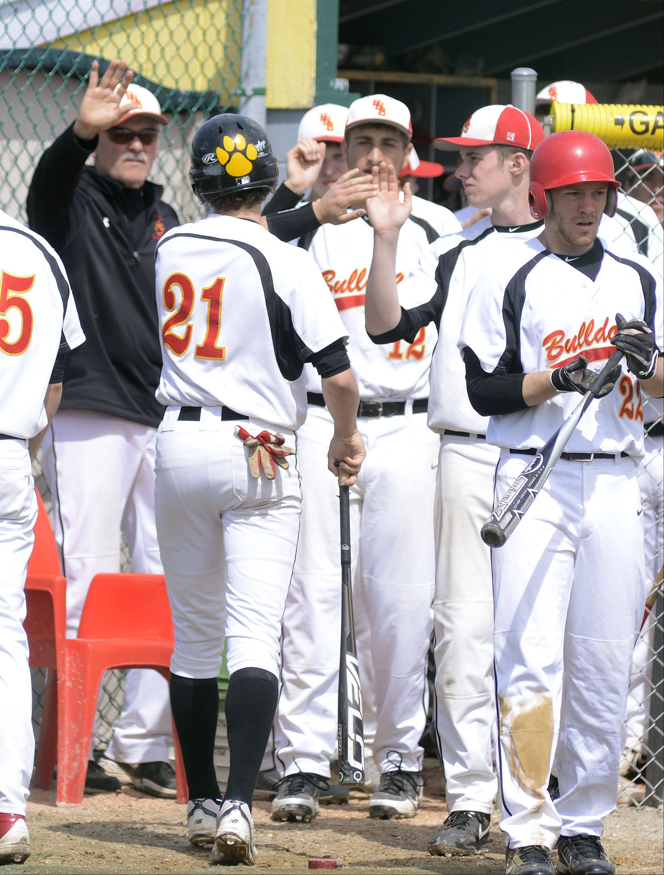 Batavia's Jeremy Schoessling gets high fives as he comes back to the dugout after scoring a run in the in the fourth inning on Saturday, May 4.
