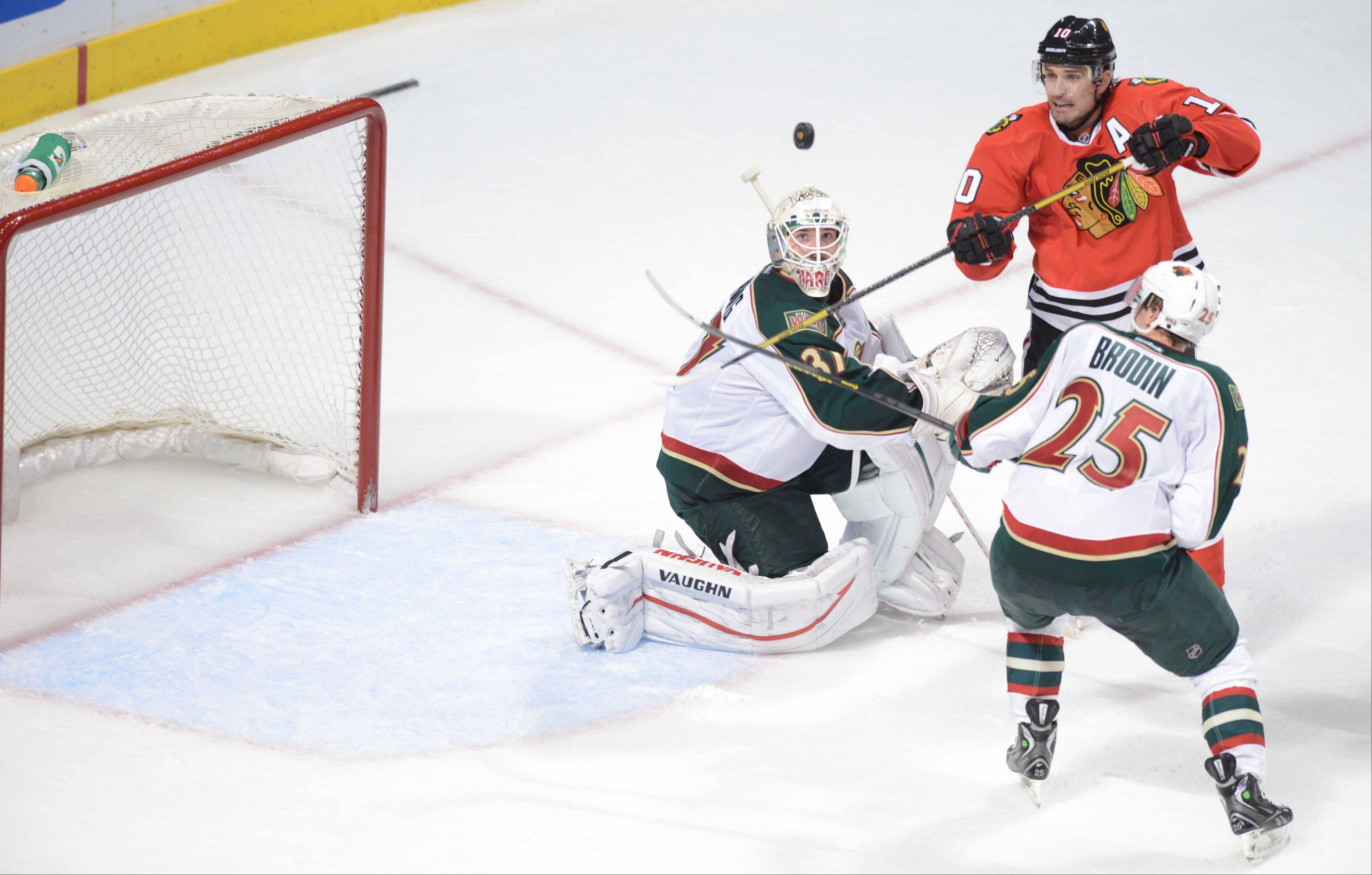 Patrick Sharp attempts to score against the defense of Jonas Brodin and Josh Harding during Game 2 of the Hawks' 5-2 win over Minnesota on Friday. The Hawks are 27-0-3 this season when Sharp is in the lineup.