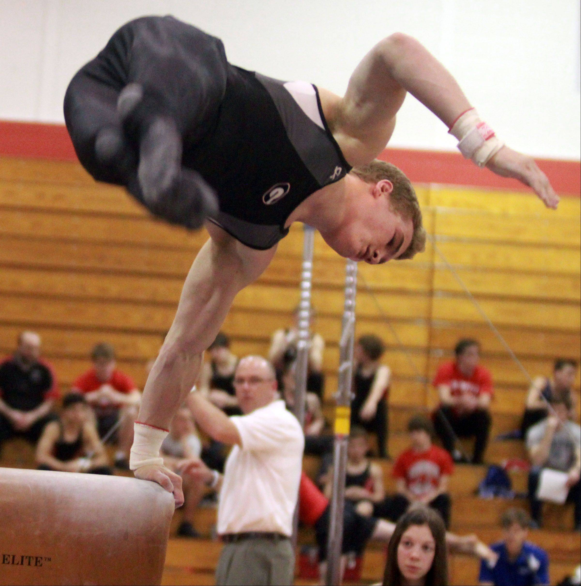 Grant's Connor Dieks dismounts from the pommel horse at the Mundelein boys gymnastics sectional on Saturday.